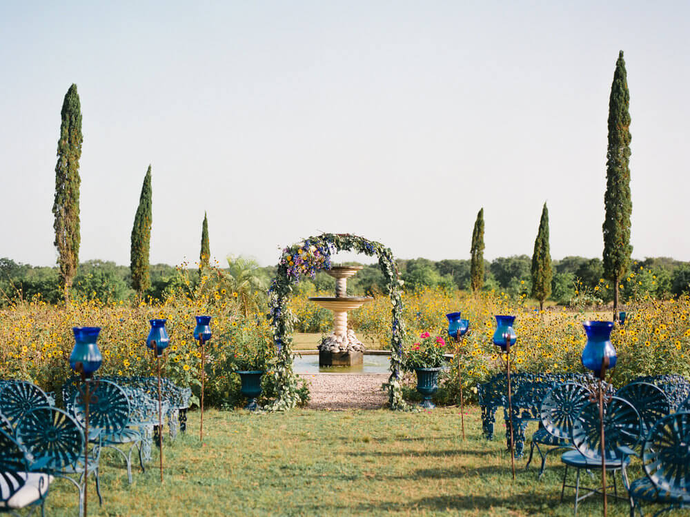 French country wedding inspiration ceremony, outdoors, blue metal chairs, fountain, floral arch.