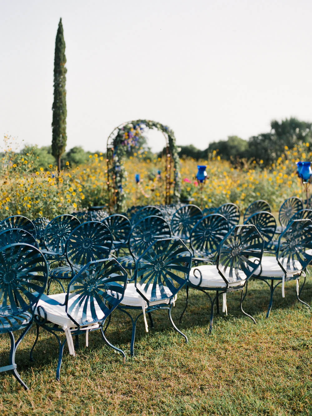 French country wedding inspiration blue metal chairs for ceremony.