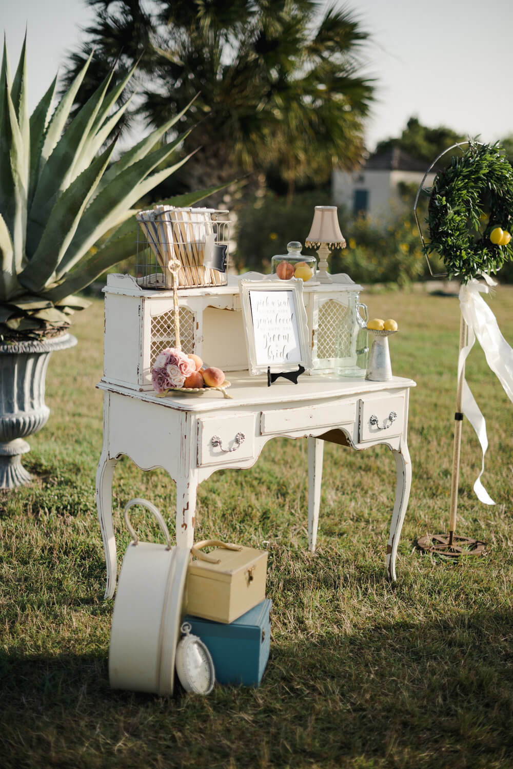French country wedding inspiration vintage desk with antique suitcases, fans, and ceremony programs.