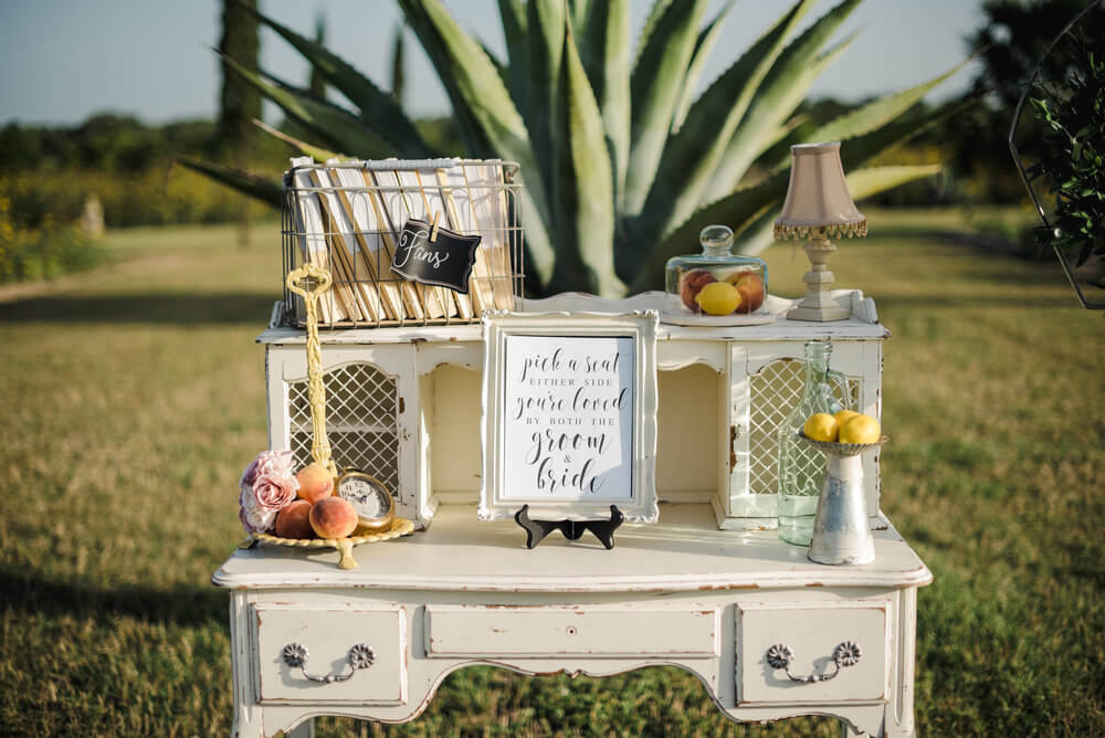 French country wedding inspiration vintage desk with antique suitcases, fans, ceremony programs, lemons, and peaches, with decor.