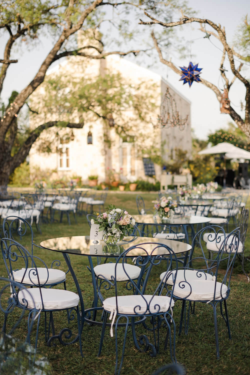 French country wedding inspiration reception area with dark blue bistro tables outdoors.