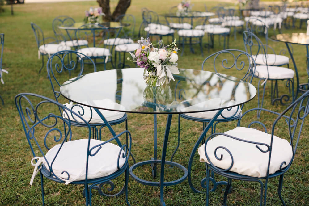 French country wedding inspiration blue bistro tables with flowers on glass tops.