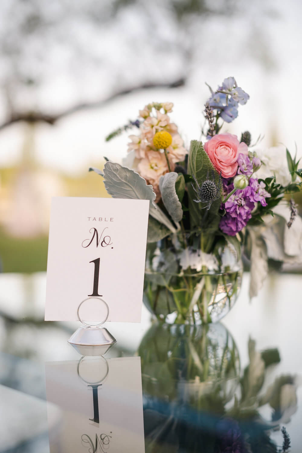 French country wedding inspiration glass table tops with table numbers and flowers.