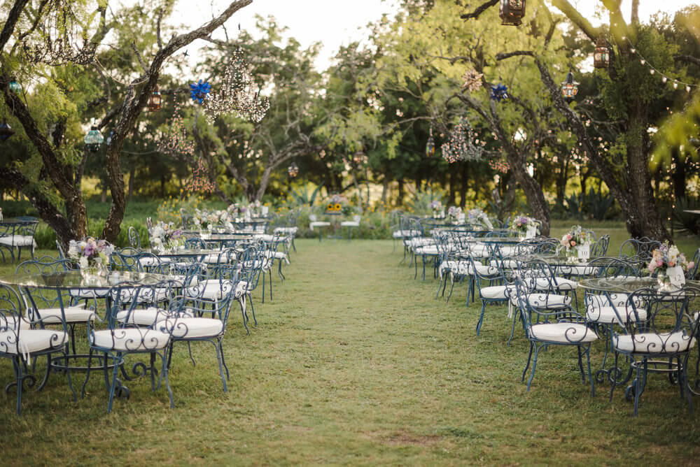 French country wedding inspiration outdoors with blue bistro tables and chairs under chandeliers, and outdoor lanterns.
