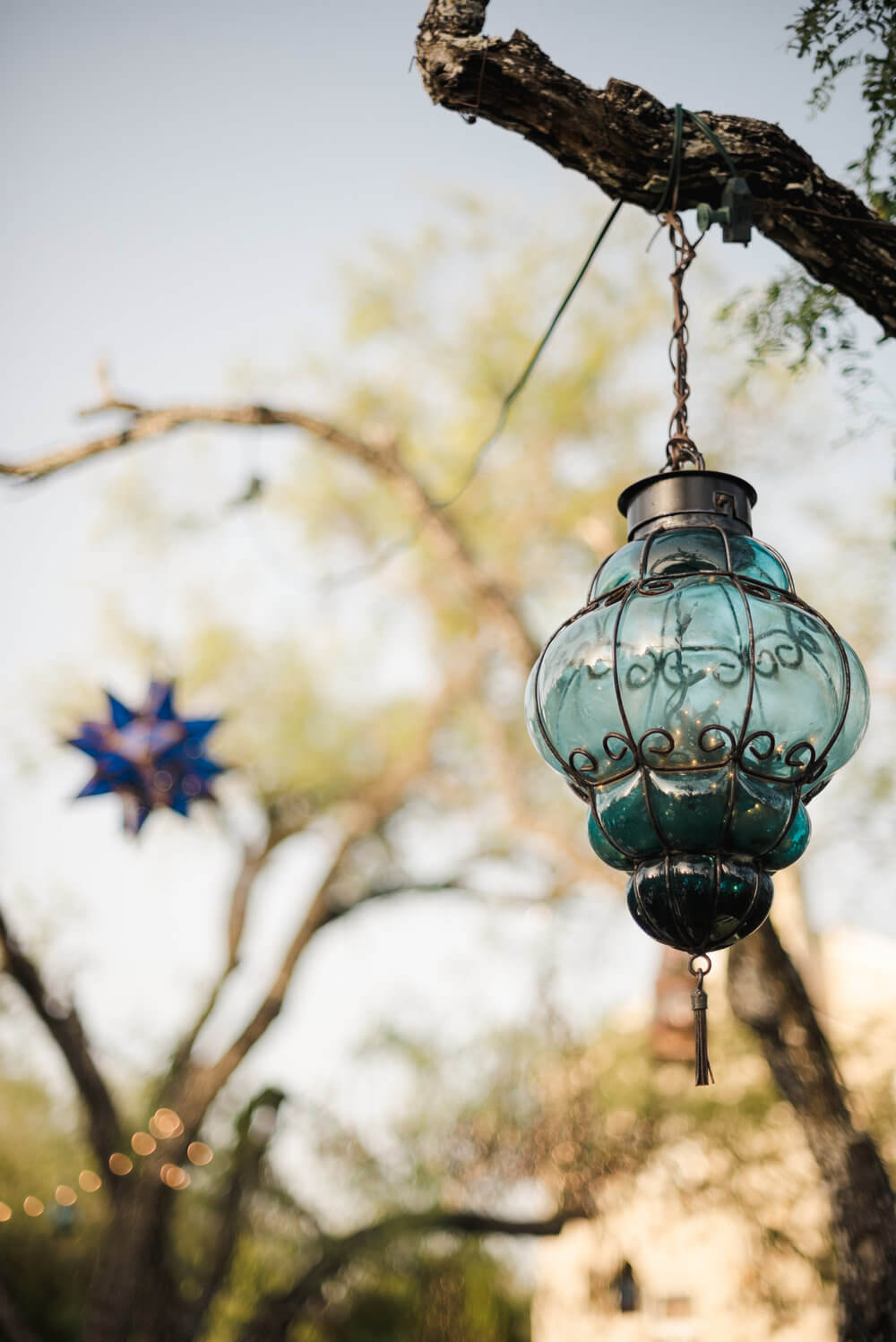 French country wedding inspiration blue glass lanterns hanging from the tree branches.
