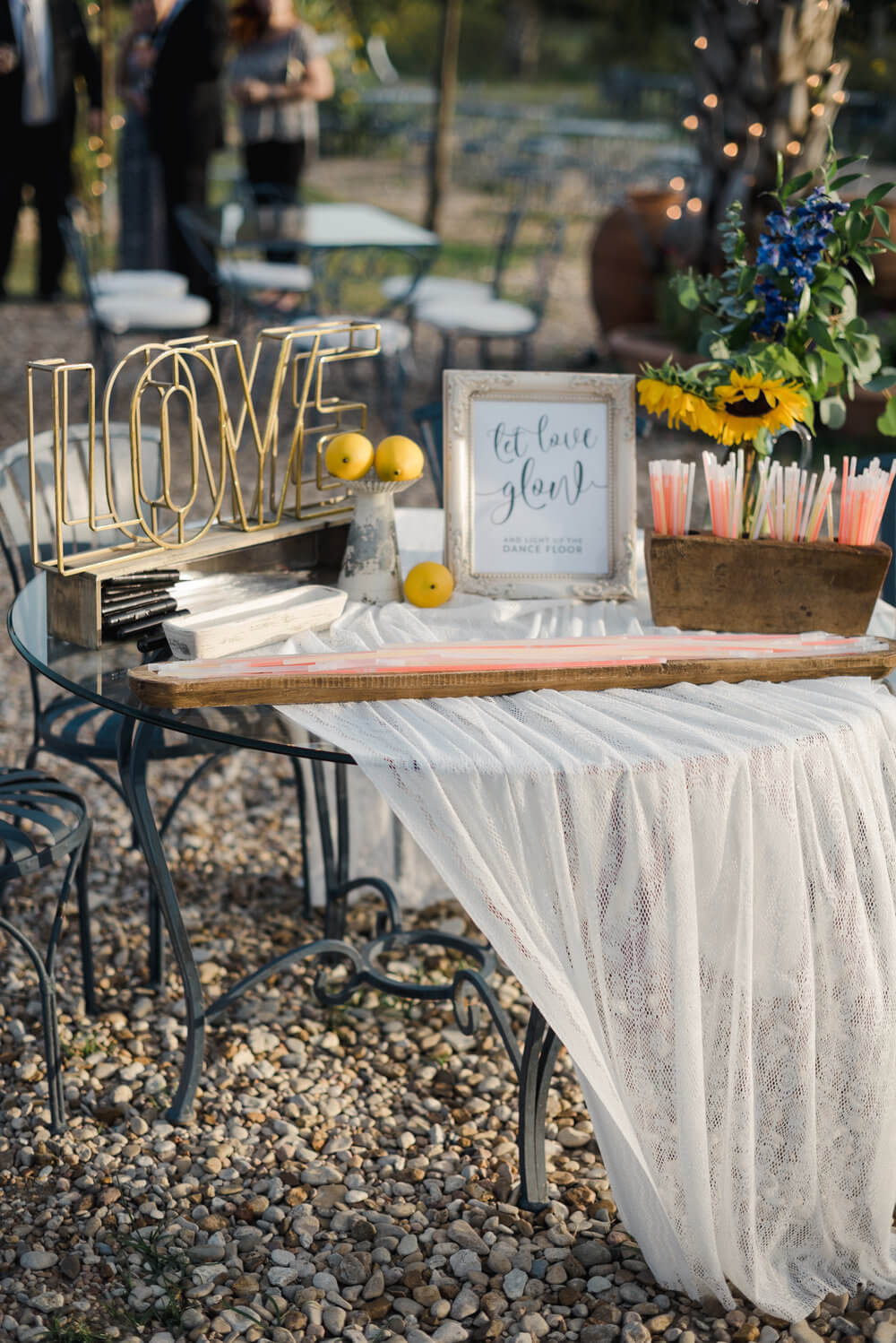 French country wedding inspiration styled table with glow sticks and props.