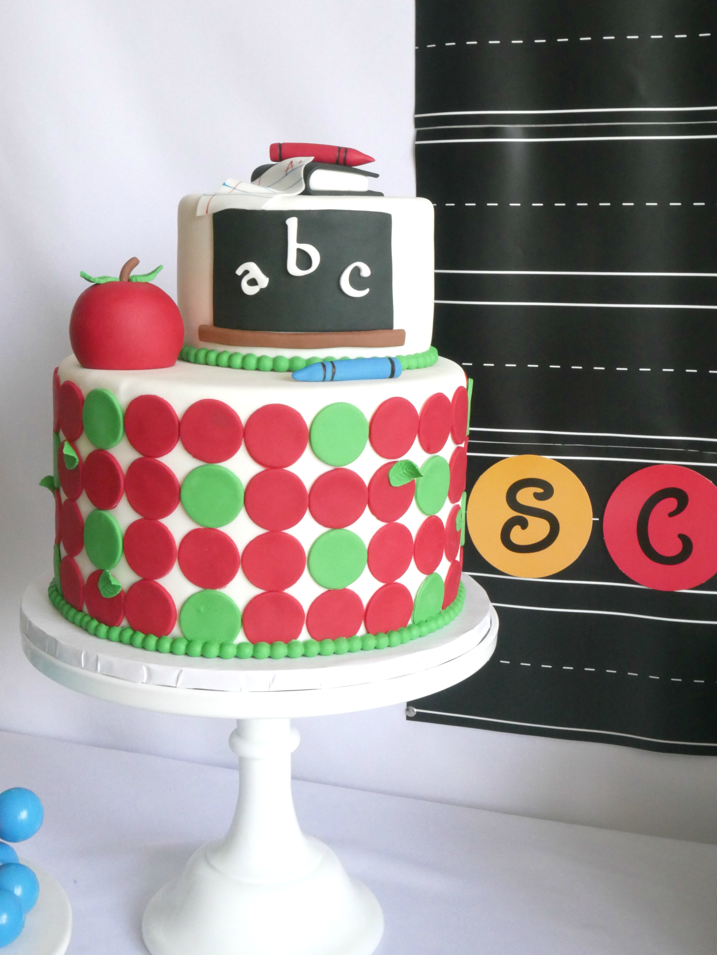 Back to School party cake with polka dots, apples, and a chalkboard theme. The cutest school themed cake with decorations made of fondant and modeling chocolate in primary colors. See all the details on Mint Event Design www.minteventdesign.com #backtoschool #backtoschoolideas #kidsparty #kidspartyideas #kidsparties #partycakes
