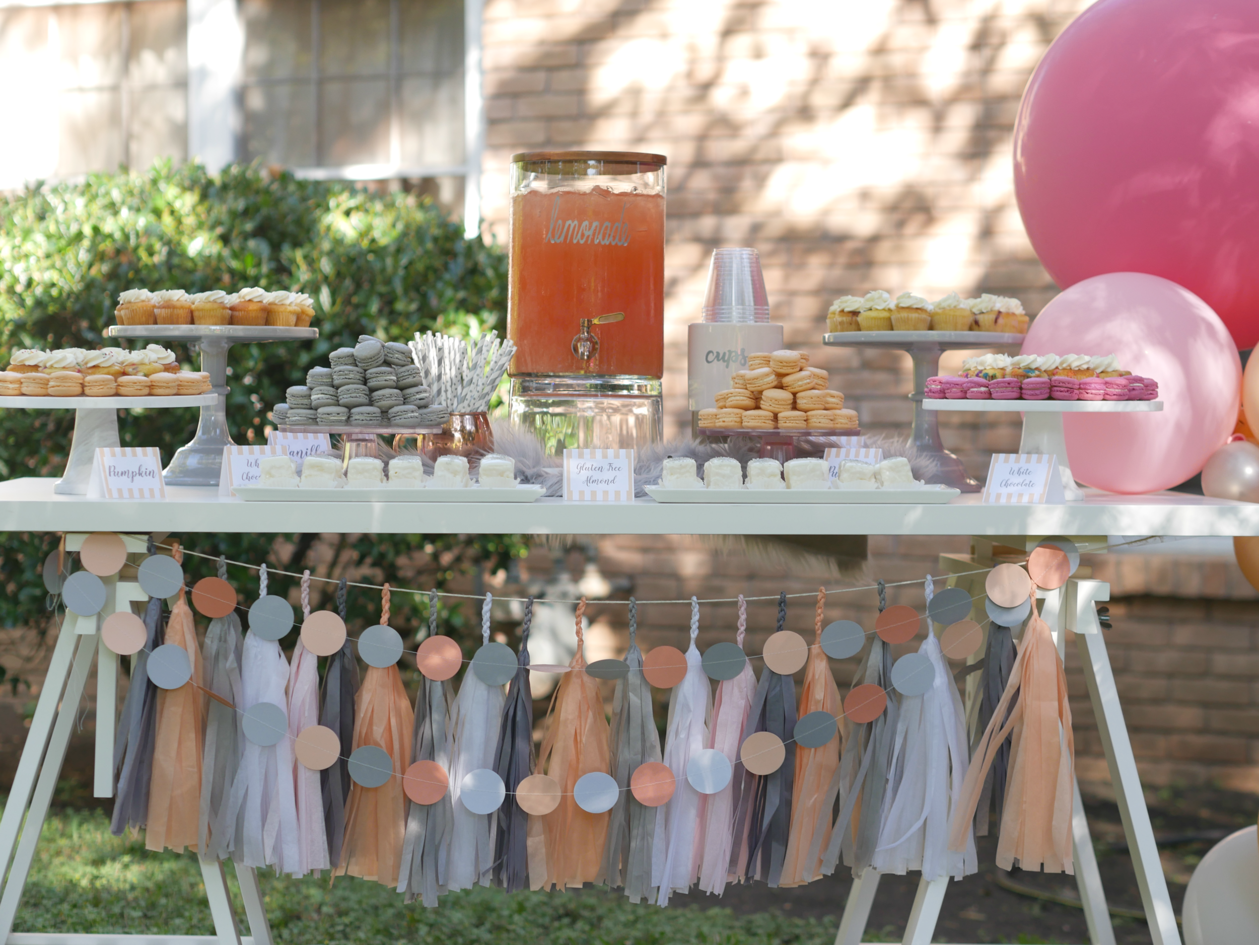 Gray and peach dessert table at an Austin area neighborhood block party with a balloon garland and a lemonade stand.