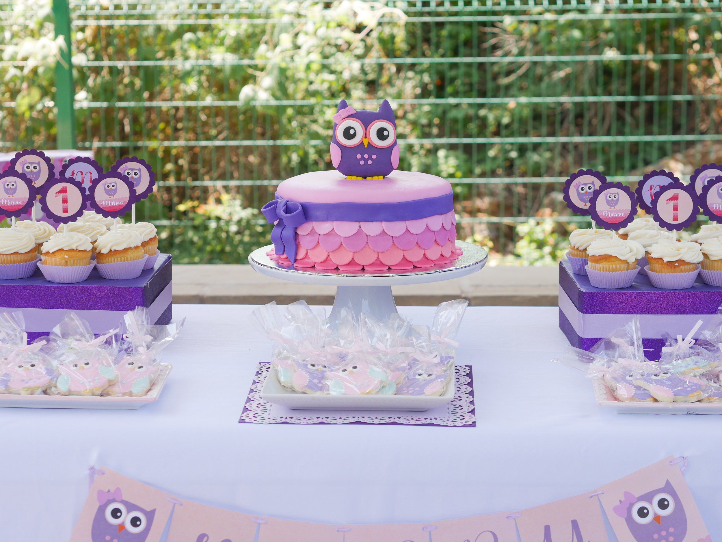 Come see this Ombre Pink and Purple Owl Themed first birthday party. This adorable owl birthday cake takes center stage on the dessert table and features scalloped frosting to resemble feathers. Click to see the entire party styled by party stylist Mint Event Design. #birthdayparty #partyideas #partyinspiration #owl #birthdaycake #desserttable