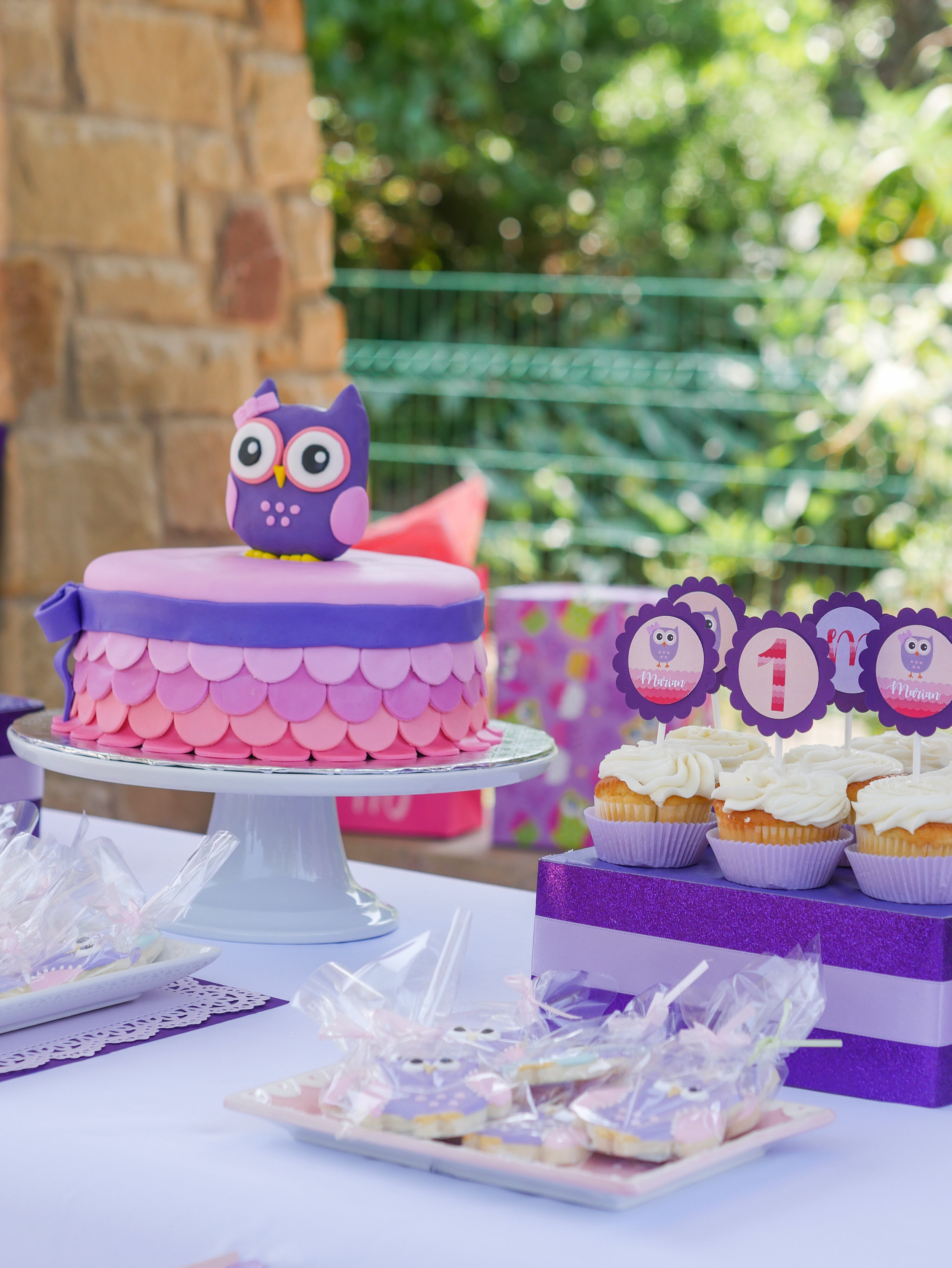 Cute Pink and Purple desserts table at an owl first birthday party. Full details on this look whoo's one birthday party can be found on www.minteventdesign.com - by party stylist Mint Event Design in Austin, Texas. #birthdayparty #partyideas #partyinspiration #owl #firstbirthday #owlcake #birthdaycake #partycupcakes