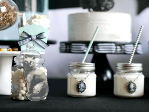 Unexpected details at your Halloween Party create fun surprises for your guests. Here there's a black cat on a jar and skeleton cameos hanging on mason jar drinks. Come see even more Halloween party tips from stylist Mint Event Design. #halloweenparty #partyideas #partyinspiration #halloween #halloweenideas #halloweendrinks #halloweendecorations