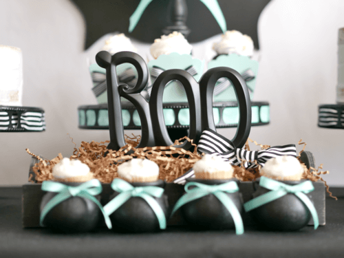 """This """"Boo"""" sign adds a fun touch to this cute and modern Halloween Party. Aren't those mini cauldrons just the cutest cupcake holder? Come see even more Halloween party ideas from stylist Mint Event Design. #halloweenparty #partyideas #partyinspiration #halloween #halloweenideas #halloweendecorations #halloweencupcakes"""