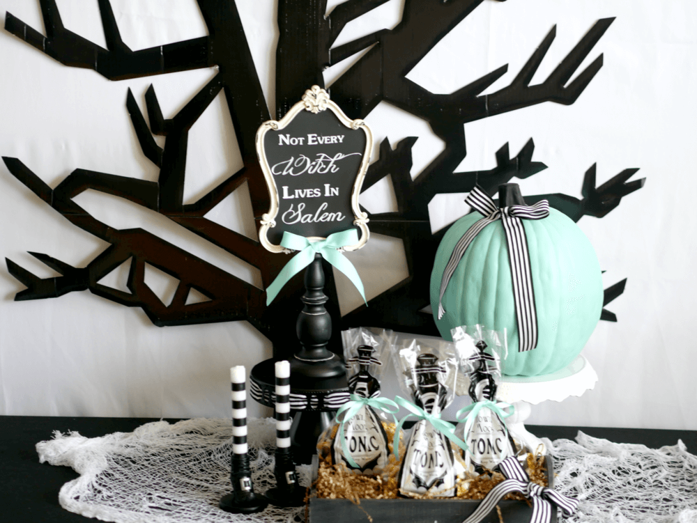 Fun treat bag station for a Halloween party! This black tree silhouette was the perfect accent to the party favor table at this modern Halloween Party in black and teal colors. Click to see what the tonic party favor bags had inside of them on the Mint Event Design blog. #halloweenparty #partyideas #partyinspiration #halloween #halloweenideas #halloweendecorations #halloweensdesserts #halloweenfavors #partyfavors