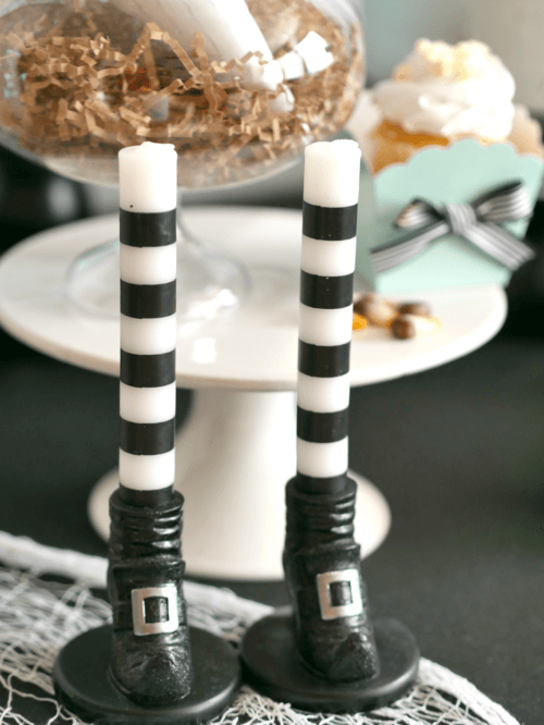These witch feet candles are so cute! What a fun touch to the Halloween Party table. Click to see all the fun party details from this Modern Halloween Party on the Mint Event Design blog. #halloweenparty #partyideas #partyinspiration #halloween #halloweenideas #halloweendecorations #halloweensdecor