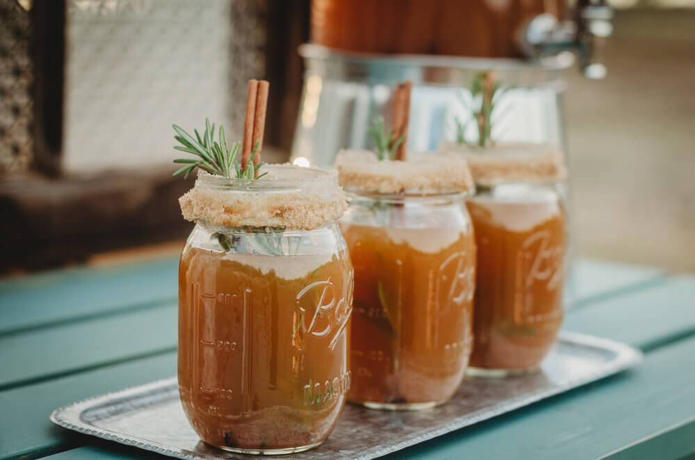 The Prettiest Fall drink presentation: Coat the mason jar rim with cinnamon and sugar and add a cinnamon stick for the drink stirrer. Click to see even more details of this fall bridal shower by party stylist Mint Event Design. #bridalshowers #bridalshowerideas #rusticwedding #rusticbridalshower #bridalshowerdecor #farmwedding #drinks #drinkstation #cocktail
