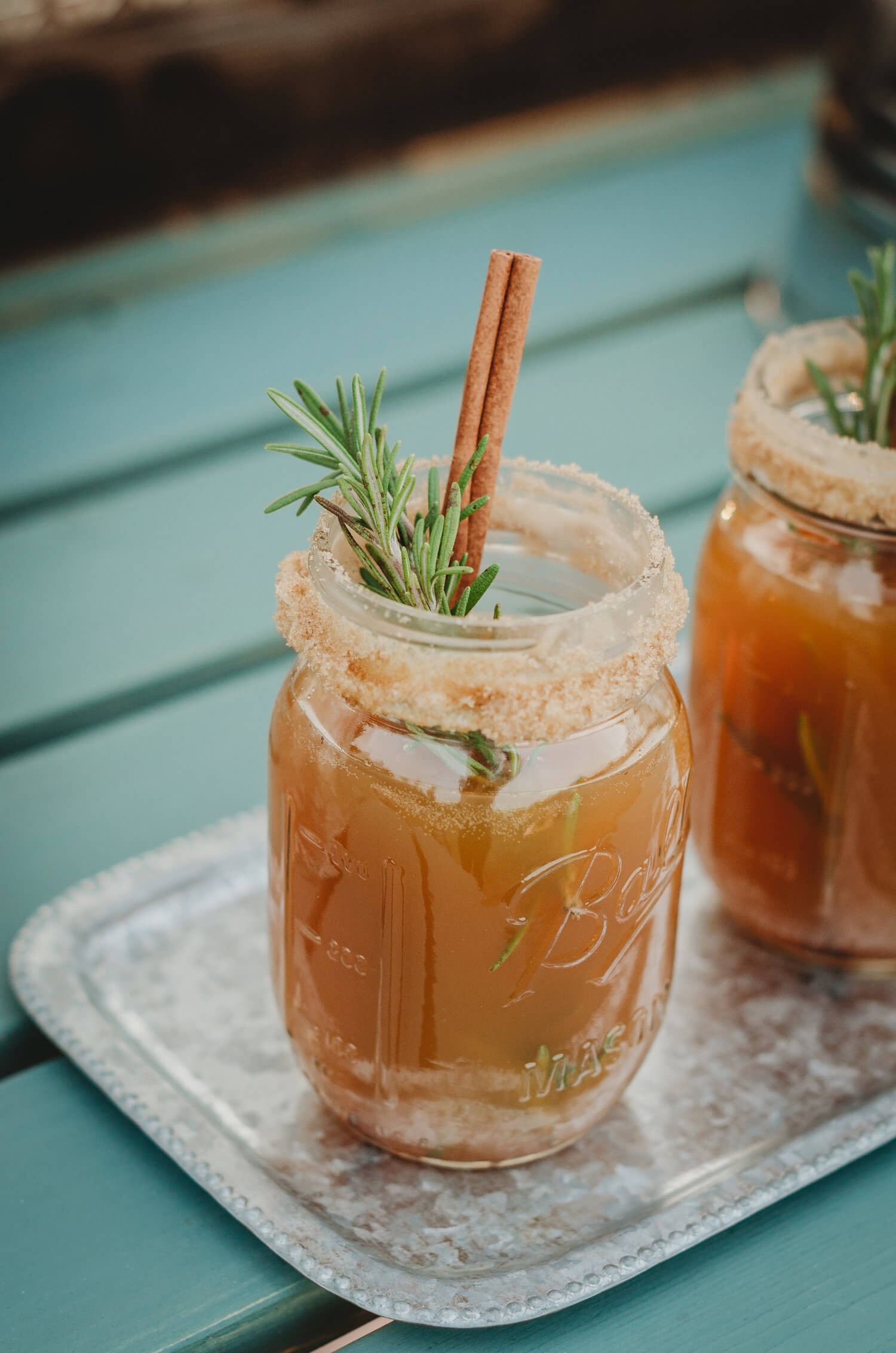 The Best Way to Serve Fall Drinks: Coat the mason jar rim with cinnamon and sugar and add a cinnamon stick for the drink stirrer. Click to see even more details of this fall bridal shower by party stylist Mint Event Design. #bridalshowers #bridalshowerideas #rusticwedding #rusticbridalshower #bridalshowerdecor #farmwedding #drinks #drinkstation #cocktail