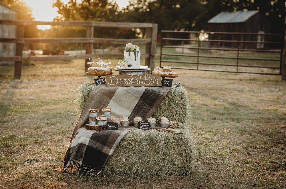 Hay bales create the perfect tables for this rustic bridal shower dessert bar. Created by party stylist Mint Event Design. #bridalshowers #bridalshowerideas #rusticwedding #rusticbridalshower #bridalshowerdecor #farmwedding #partyideas #fallbridalshower #dessertbar