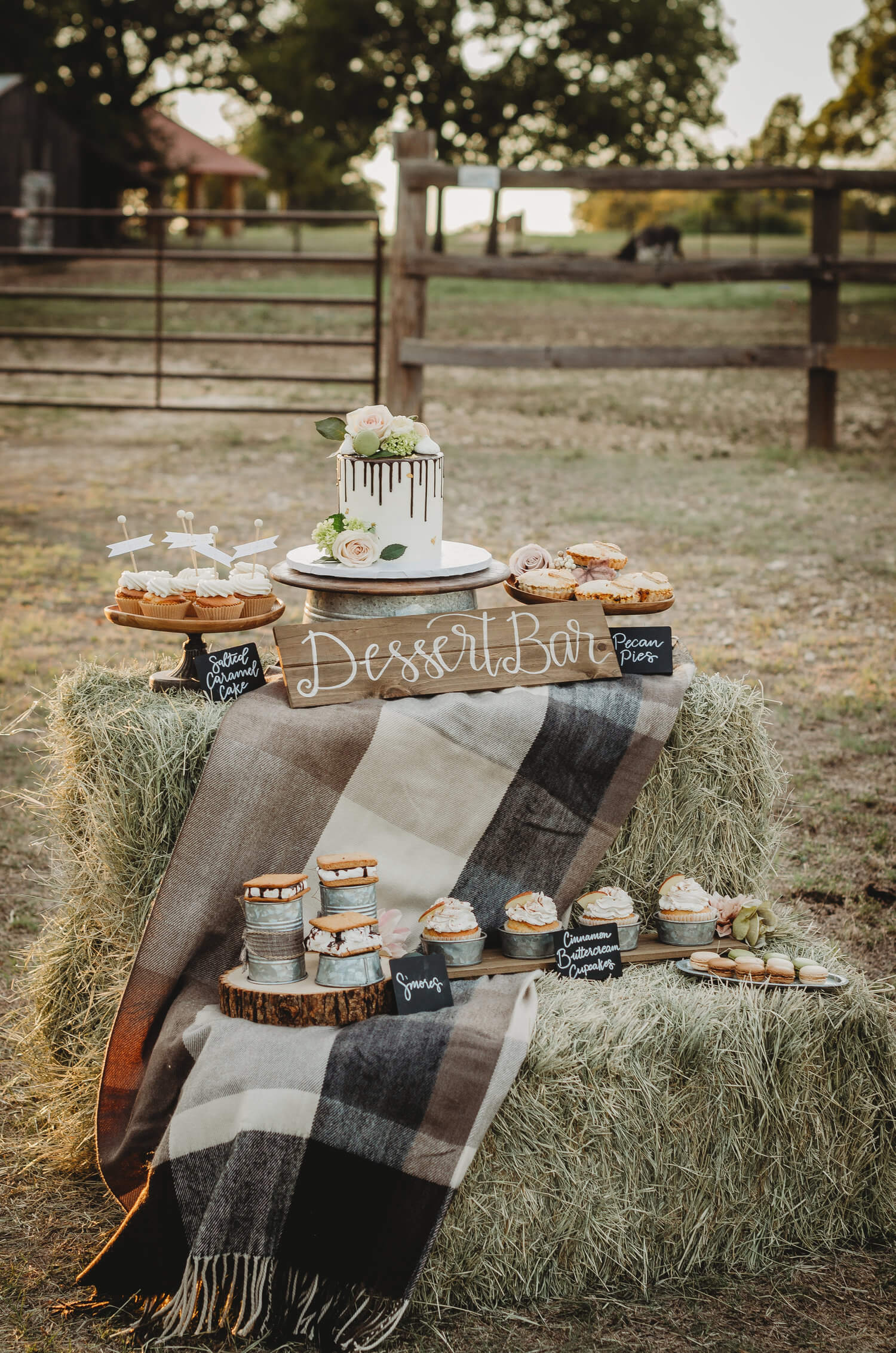 This rustic bridal shower dessert bar is created on hay bales with a flannel throw. Lots more bridal shower ideas from this Fall in Love party theme can be found on the Mint Event Design Blog www.minteventdesign #bridalshowers #bridalshowerideas #rusticwedding #rusticbridalshower #bridalshowerdecor #farmwedding #partyideas #fallbridalshower #dessertbar #bridaslshowerdessert #minidesserts