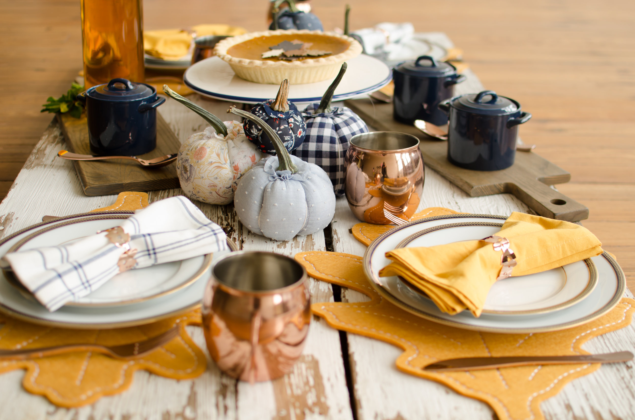 Rustic and Chic Thanksgiving table inspiration in copper and blue with fabric covered pumpkins in a variety of patterns for extra fun on the tablescape. See more Thanksgiving Party Ideas from party planner, Mint Event Design in Austin, Texas on www.minteventdesign.com #thanksgiving #thanksgivingdecorations #tablescape #thanksgivingtable #pumpkins #tablesettings #fallparty