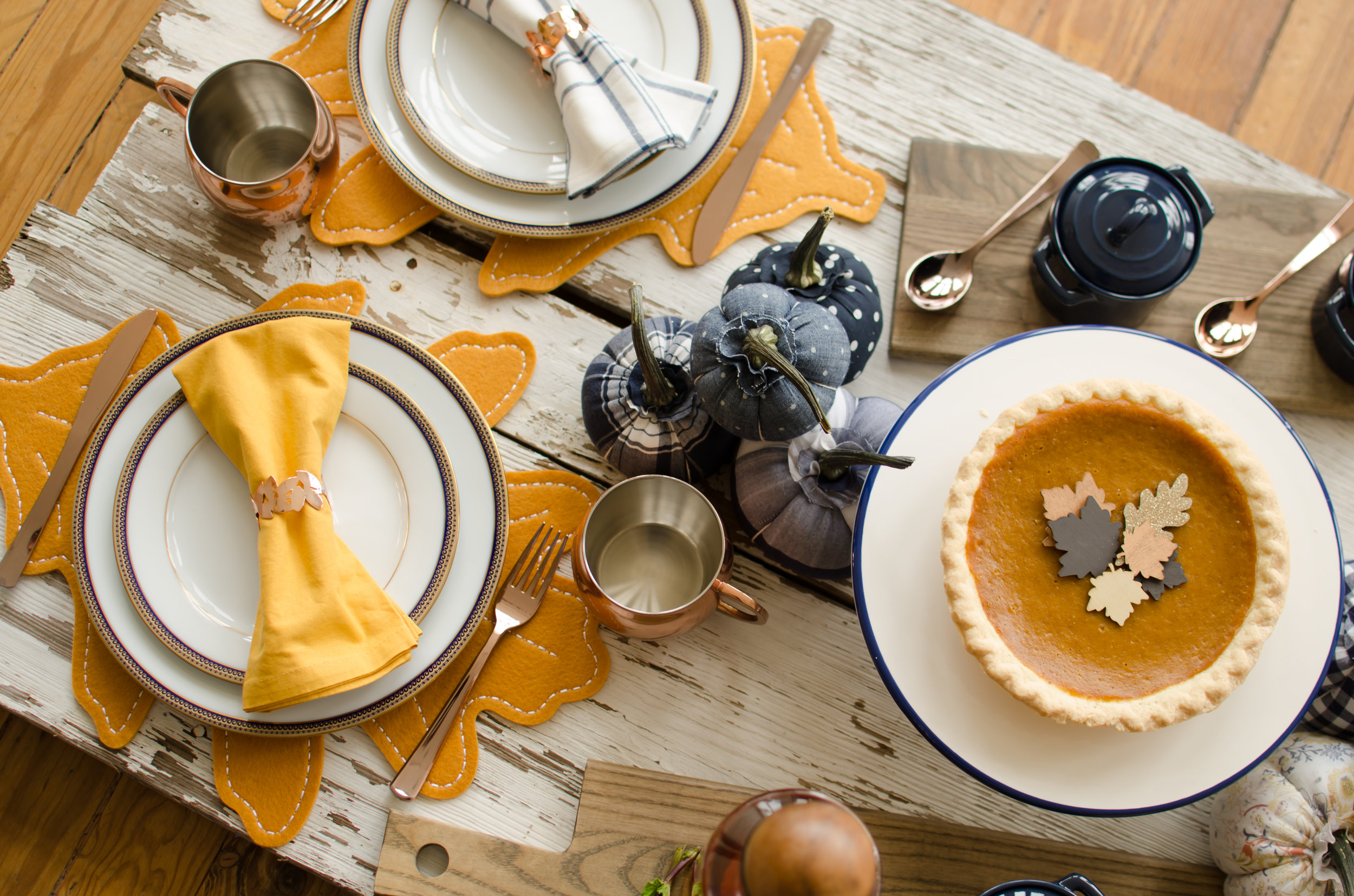 Thanksgiving table styling ideas including colors of blue and copper with fabric covered pumpkins. Click to see how to combine cozy and rustic decorations with your Thanksgiving Table Setting from party planner, Mint Event Design in Austin, Texas on www.minteventdesign.com #thanksgiving #thanksgivingdecorations #tablescape #thanksgivingtable #pumpkins #tablesettings #fallparty from Mint Event Design