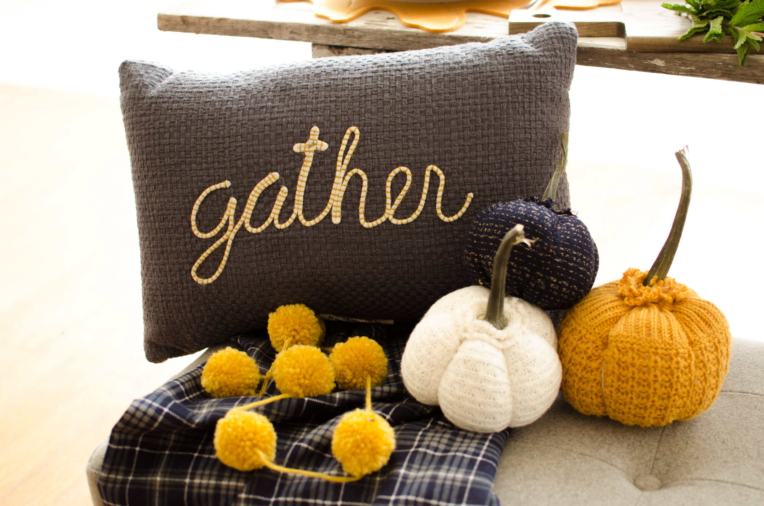 Fabric pumpkins and cozy elements like this plaid throw really add charm to this Thanksgiving table setting. See more Thanksgiving Party Ideas from party planner, Mint Event Design in Austin, Texas on www.minteventdesign.com #thanksgiving #thanksgivingdecorations #tablescape #thanksgivingtable #pumpkins #tablesettings #fallparty
