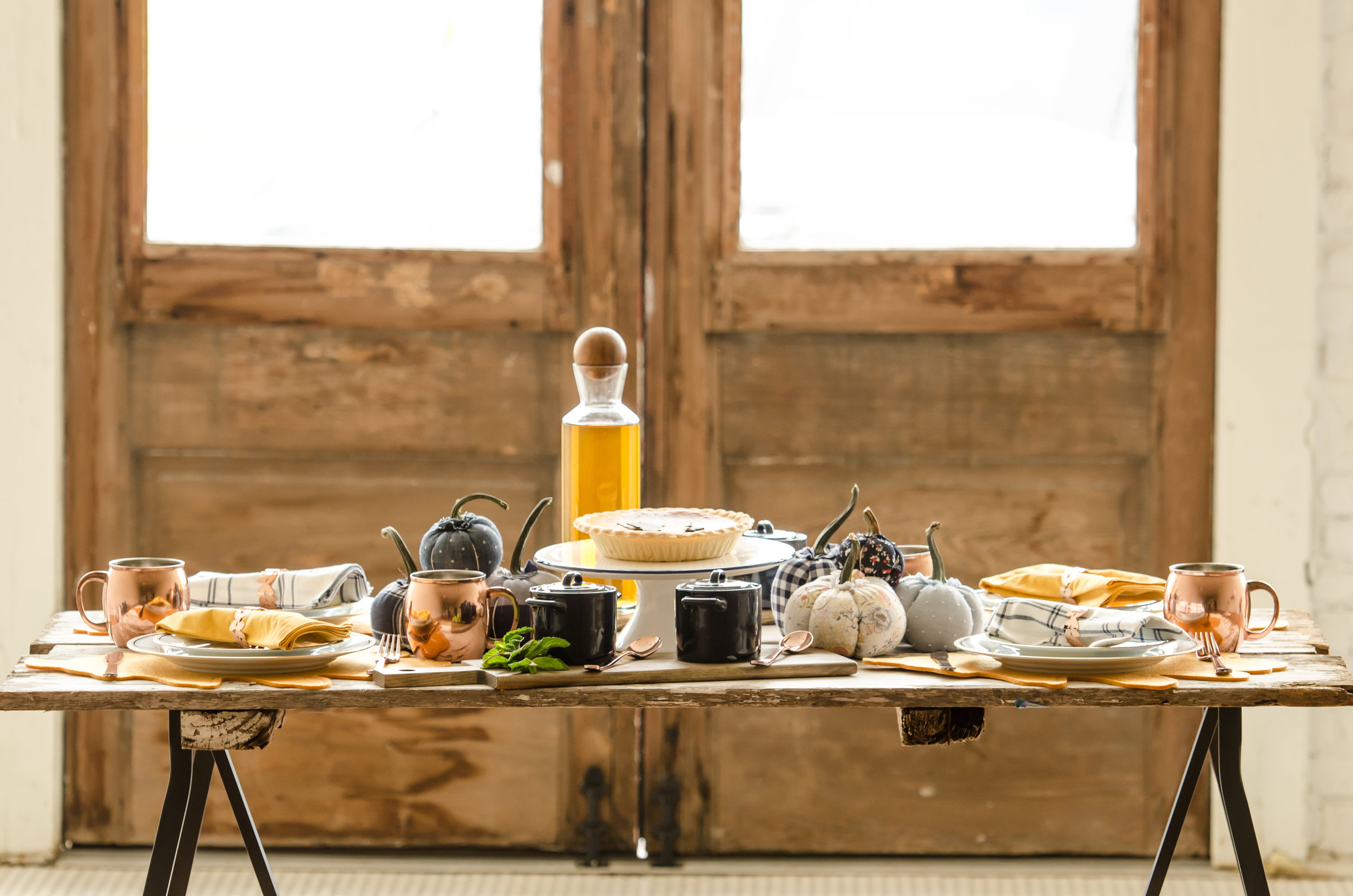 The prettiest of Thanksgiving Table Settings with fabric pumpkins for decorations, leaf placemats, cutting boards for serving the sides and die cut leaf napkin rings / see more Thanksgiving Pictures from party planner, Mint Event Design in Austin, Texas on www.minteventdesign.com #thanksgiving #thanksgivingdecorations #tablescape #thanksgivingtable #pumpkins #tablesettings #fallparty