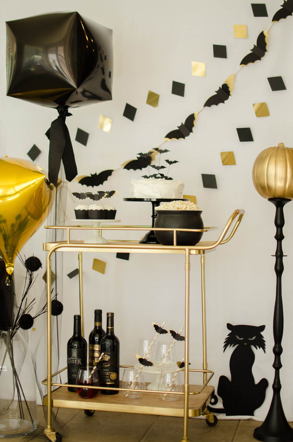 A color palette of Black, White, and Gold add spooky elegance to this adult themed Halloween party. Click to see more from this Bar Cart styled by party stylist Carolina of Mint Event Design. #partyideas #partyinspiration #halloween #barcart #barcartdecor #partystyling