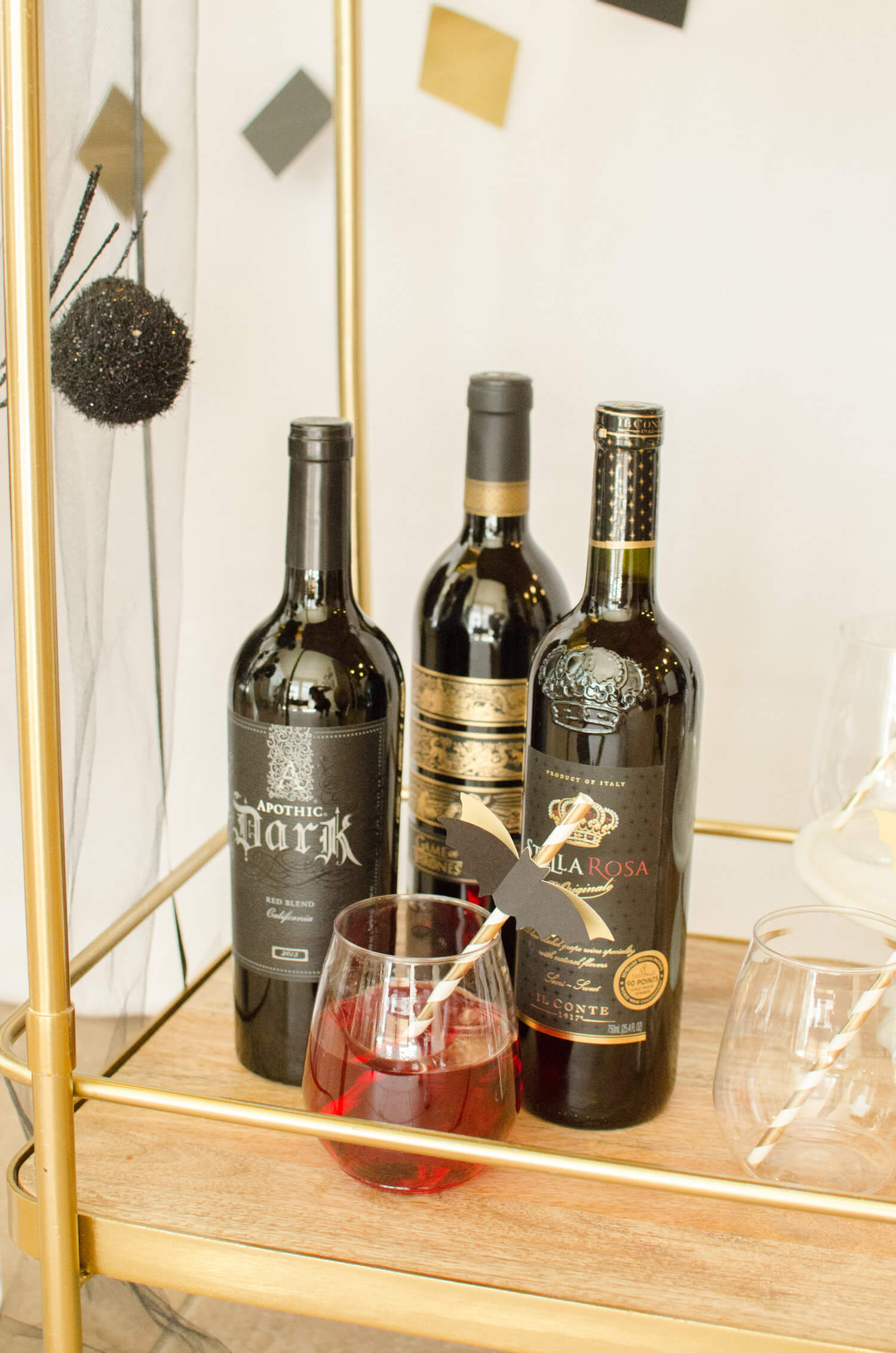 Be sure to serve Blood Red Wine at your Spooky Halloween Soiree in black wine bottles. Click for more Bar Cart styling ideas by party stylist Carolina of Mint Event Design. #partyideas #partyinspiration #halloween #partystyling #redwine #halloweenparty