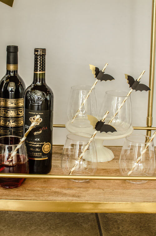 These Bat topped straws are a cute drink embellishment at this Spooky Halloween Party. Click to see more Bar Cart styling tips by party stylist Carolina of Mint Event Design. #partyideas #partyinspiration #halloween #barcart #barcartdecor #partystyling