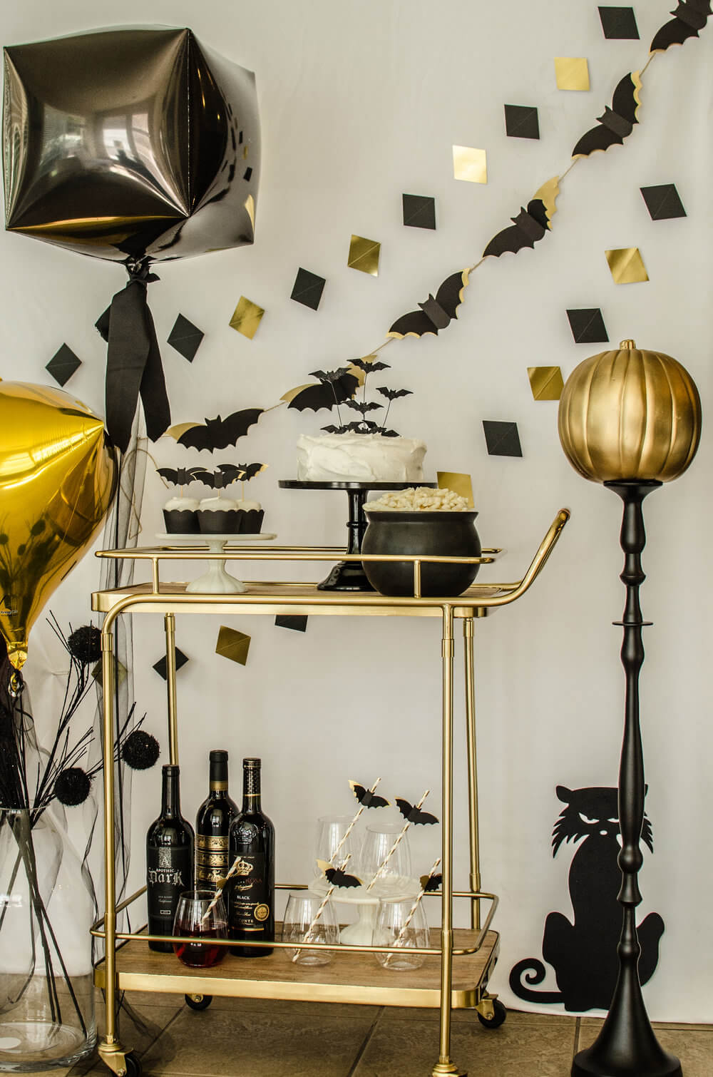 Halloween Bar Cart Styling Ideas - include drink stirrers topped with bats, a fun black cat silhouette on the wall and even a gold pumpkin on a tall stand. Click to see more from this Bar Cart styled by party stylist Carolina of Mint Event Design. #partyideas #partyinspiration #halloween #barcart #barcartdecor