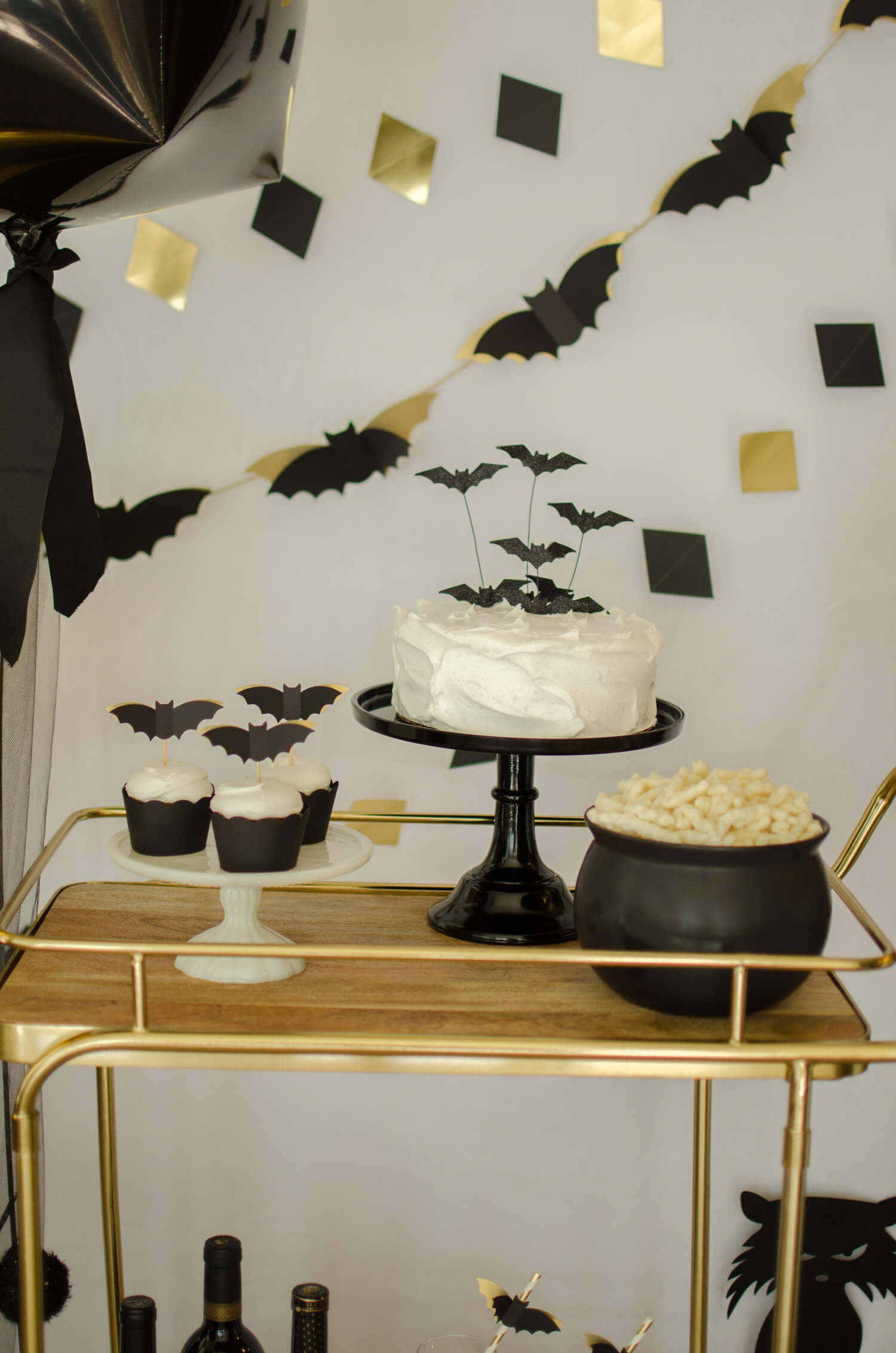 Fun Snacks at a Halloween Bash include Vanilla Cake and Cupcakes that have bat toppers. And, cheese puffs were served in a black cauldron to keep the Halloween theme going. Halloween Bar cart styling by party stylist Carolina of Mint Event Design. #partyideas #partyinspiration #halloween #cupcaketoppers #halloweensnacks