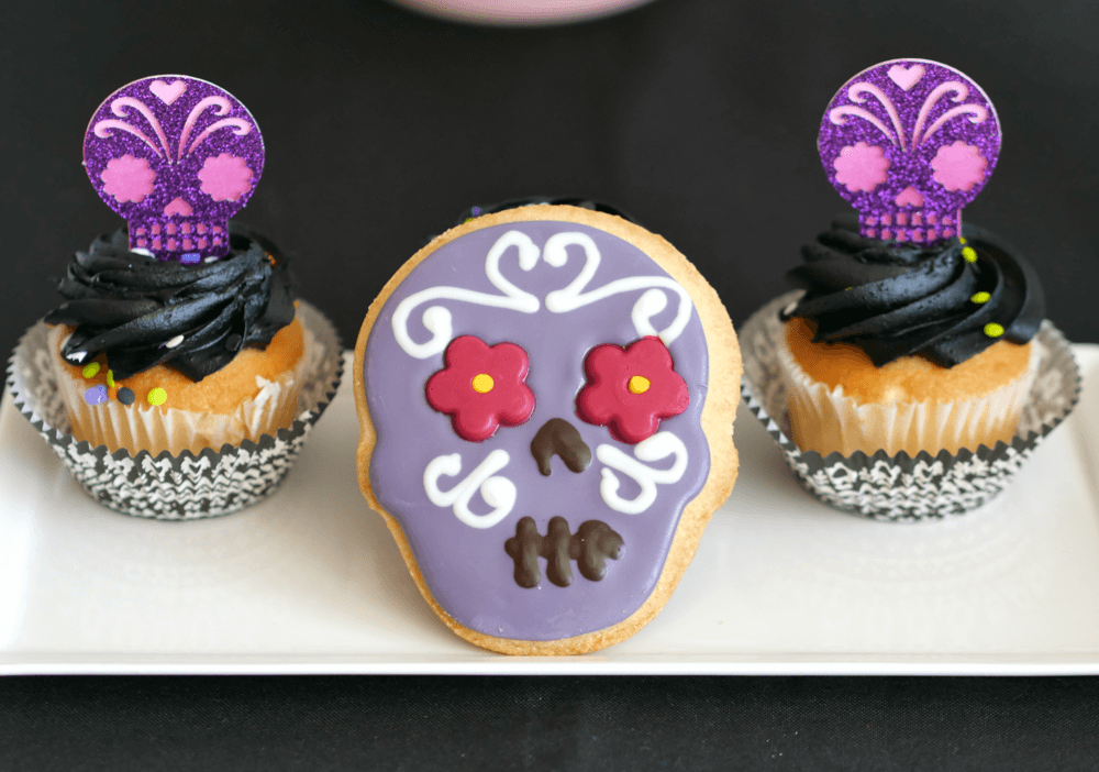 The best party sweets for a Dia de Muertos party include beautiful sugar skull cookies and cupcakes topped with black frosting and a glitter sugar skull cupcake toppers. Find more Day of the Dead party inspiration on the Mint Event Design party blog www.minteventdesign.com #dayofthedead #diadelosmuertos #sugarskulls #mexicanparty #halloweenparty #partyideas