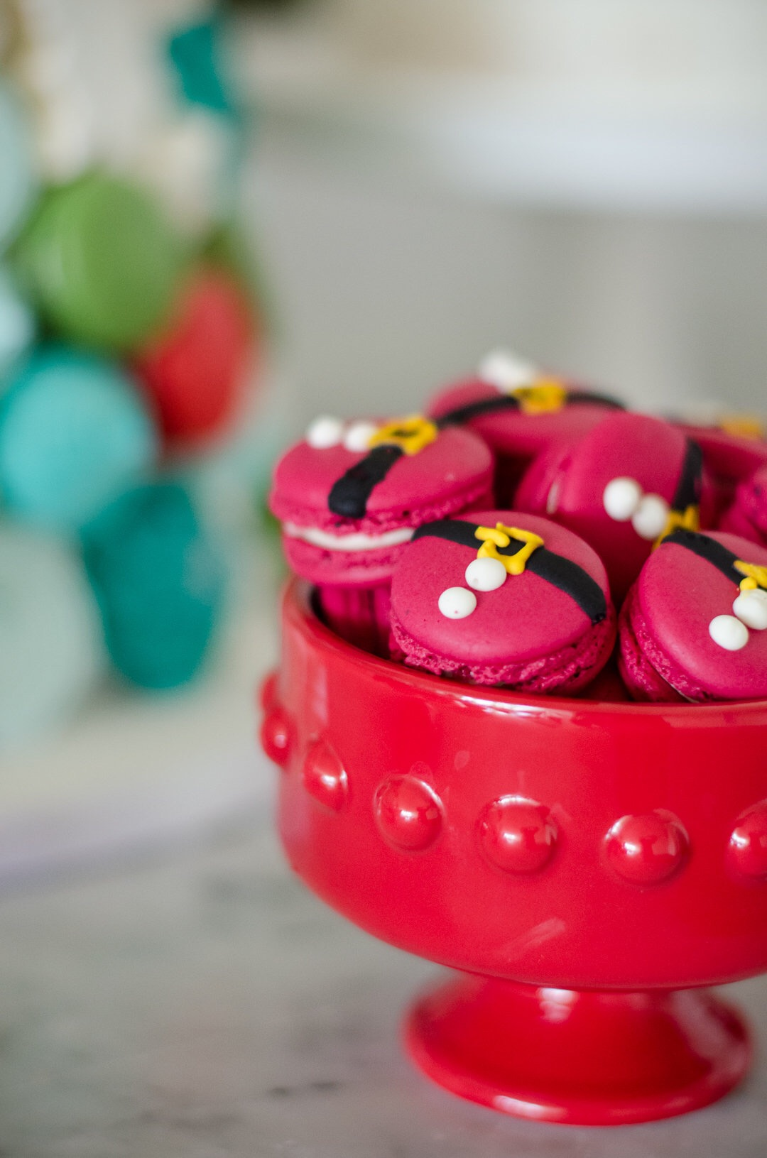 These Santa macarons are just so cute served in a pretty red footed bowl. See more holiday party inspiration from Austin based party stylist Mint Event Design at www.minteventdesign.com #desserttable #christmasdesserts #holidayparty #holidays #partyideas #christmasparty #holidaypartyideas #macarons