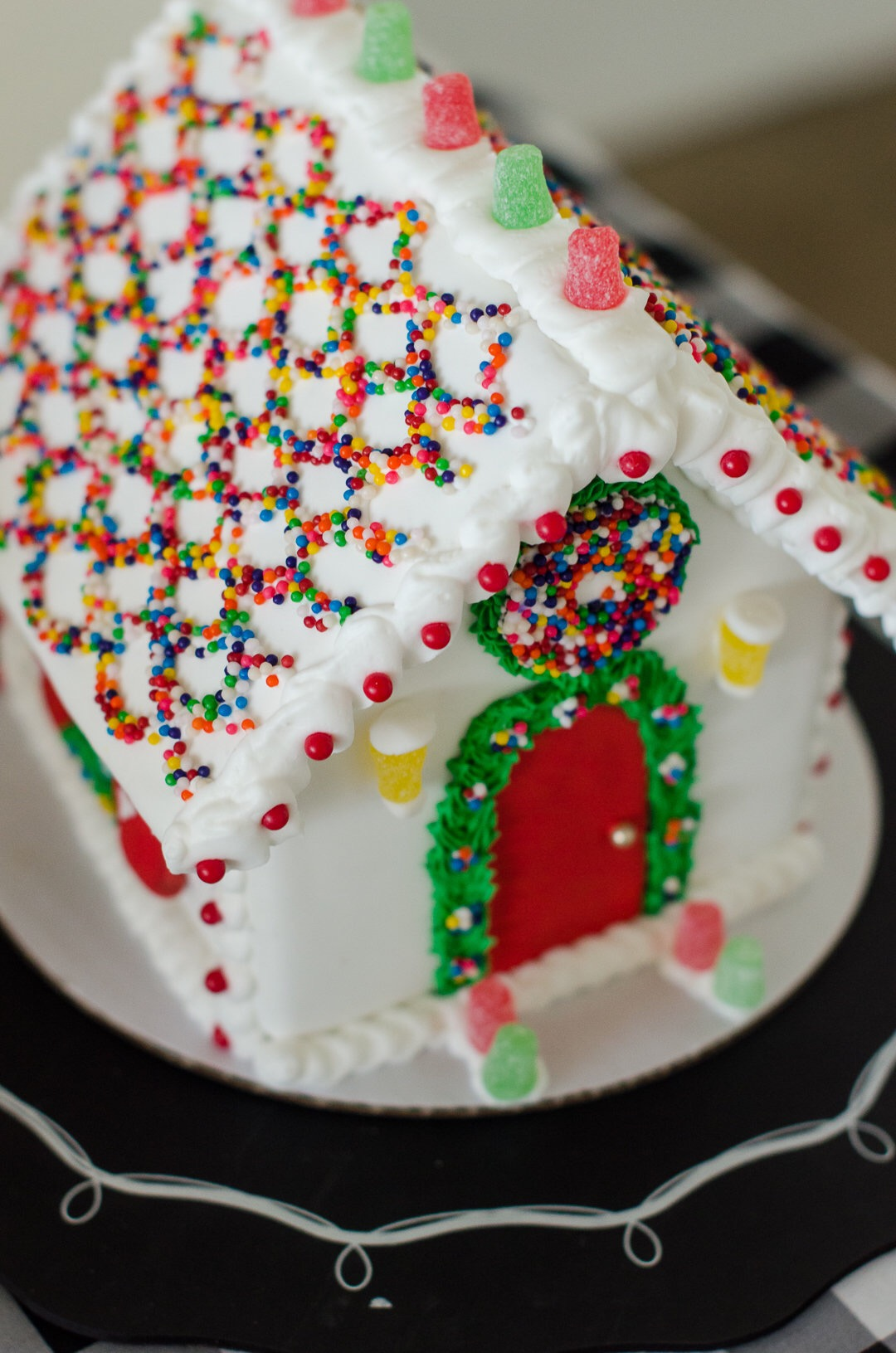 Gingerbread house professionally decorated with nonpareils. See more holiday party inspiration from Austin based party stylist Mint Event Design at www.minteventdesign.com #desserttable #christmasdesserts #holidayparty #holidays #partyideas #christmasparty #holidaypartyideas #gingerbreadhouses