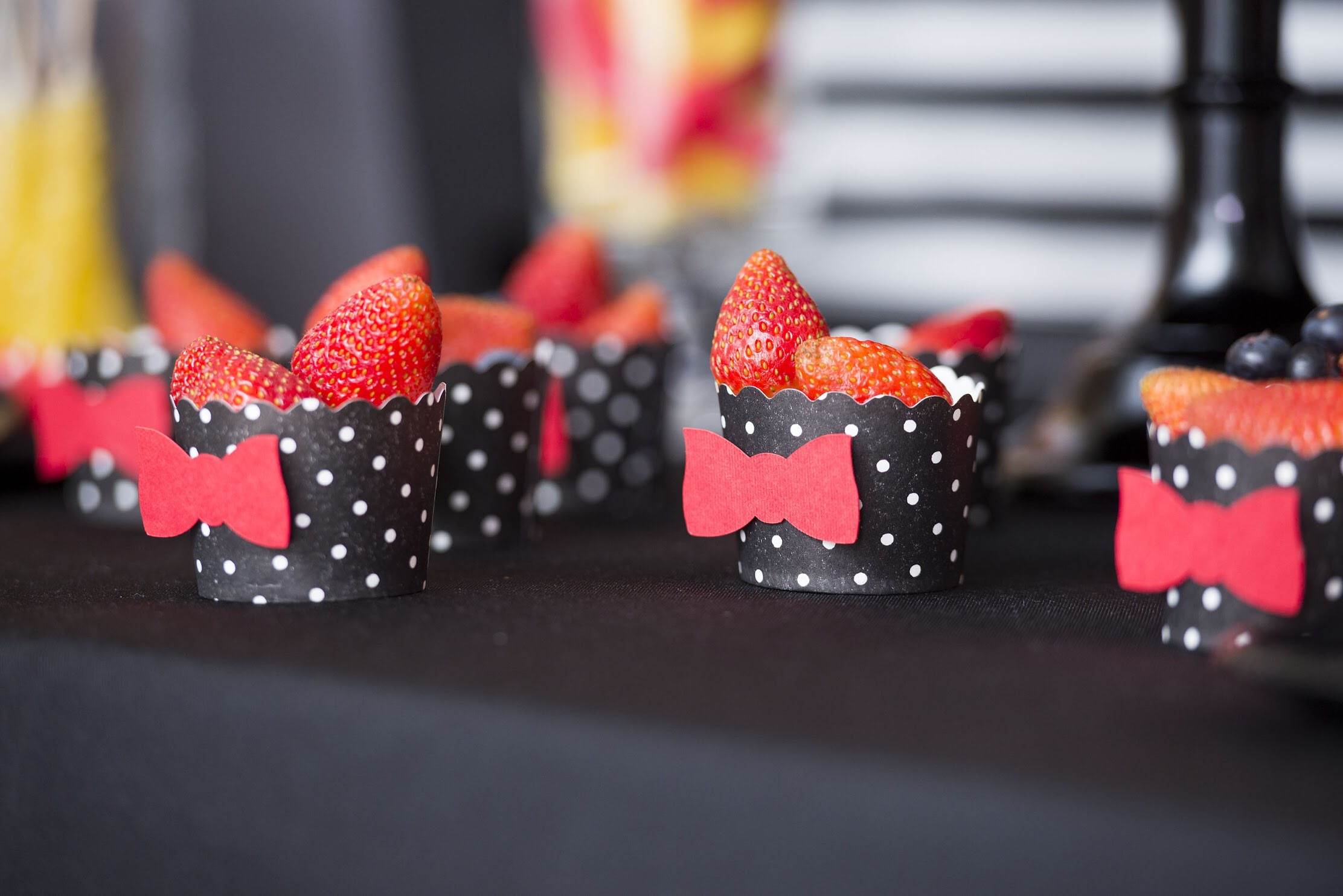 Berries for a non candy option on this dessert table are adorably Minnie themed!