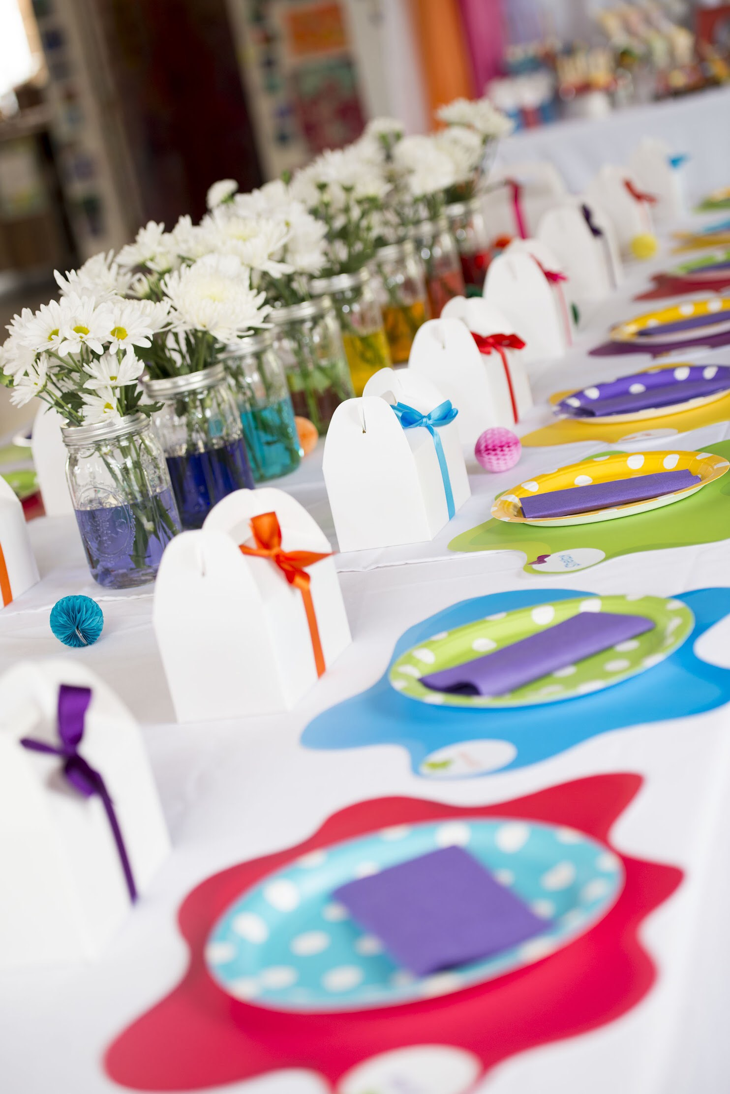 Beautifully decorated kids birthday table: white gable boxes with rainbow colored ribbons and colorful place settings along with flowers in mason jars with colored water. #kidsparty #kidspartyideas #birthdaypartyideas #artparty #rainbowparty #tablesetting