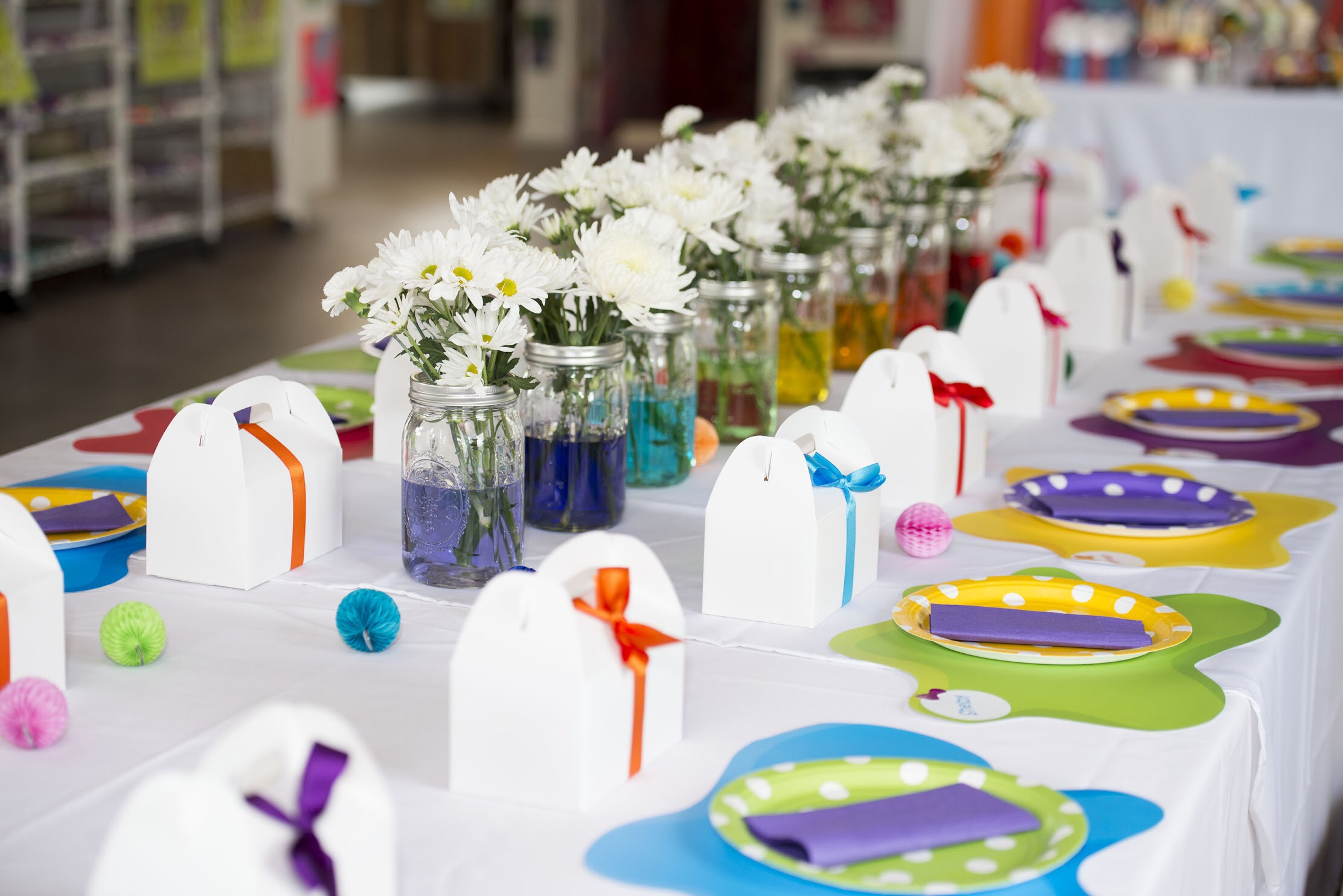 Colorful art themed birthday party features white gable favor boxes with colorful ribbon, polka dot plates and daisies in mason jars with rainbow colored water. See all the art themed party ideas on Mint Event Design www.minteventdesign.com #kidsparty #kidspartyideas #birthdaypartyideas #artparty #rainbowparty