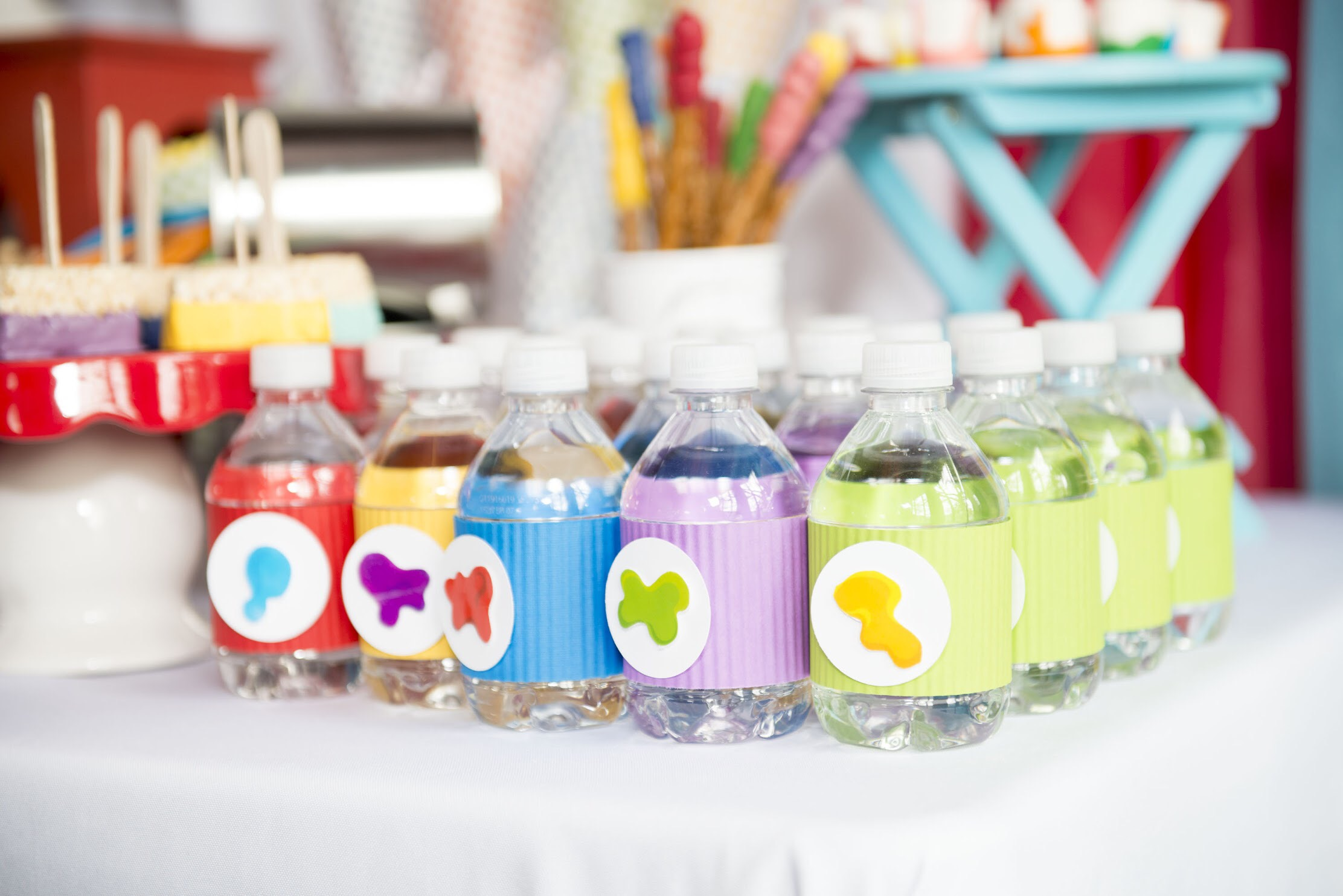 Cute rainbow colored labels on these water bottles are perfect for a little artists party. Click to see all the art themed party ideas on Mint Event Design www.minteventdesign.com #kidsparty #kidspartyideas #birthdaypartyideas #artparty #rainbowparty