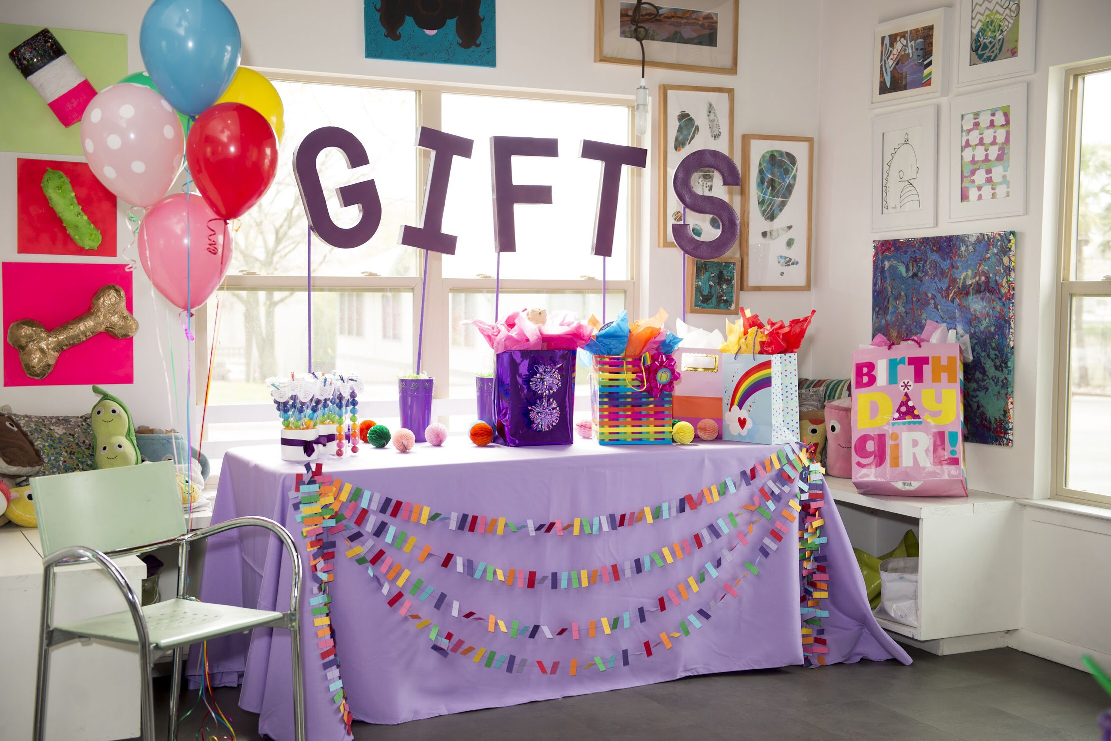 The gift table for an art themed birthday party is full of color and included GIFTS on oversized letters on sticks to be seen above the presents. See all the art themed party ideas on Mint Event Design www.minteventdesign.com #kidsparty #kidspartyideas #birthdaypartyideas #artparty #rainbowparty