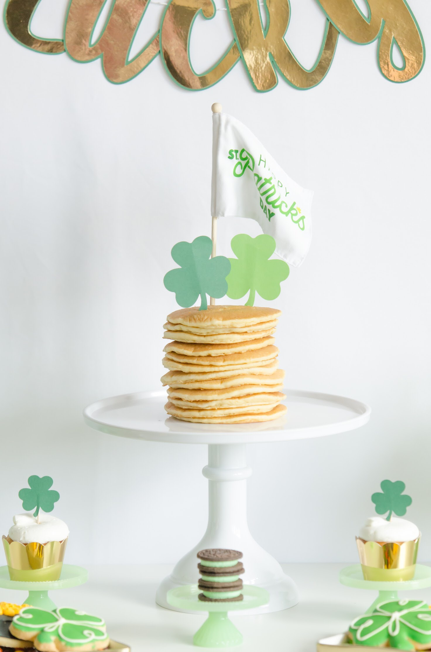 "Saint Patricks Day Breakfast Recipe: serve stacked pancakes on a cake stand, then add shamrock shaped cupcake toppers with a fun mini flag that says ""Happy St. Patrick's Day"". Via Mint Event Design www.minteventdesign.com #partyideas #partydecorations #breakfastfood #saintpatricksday #stpatricksday #pancakes"