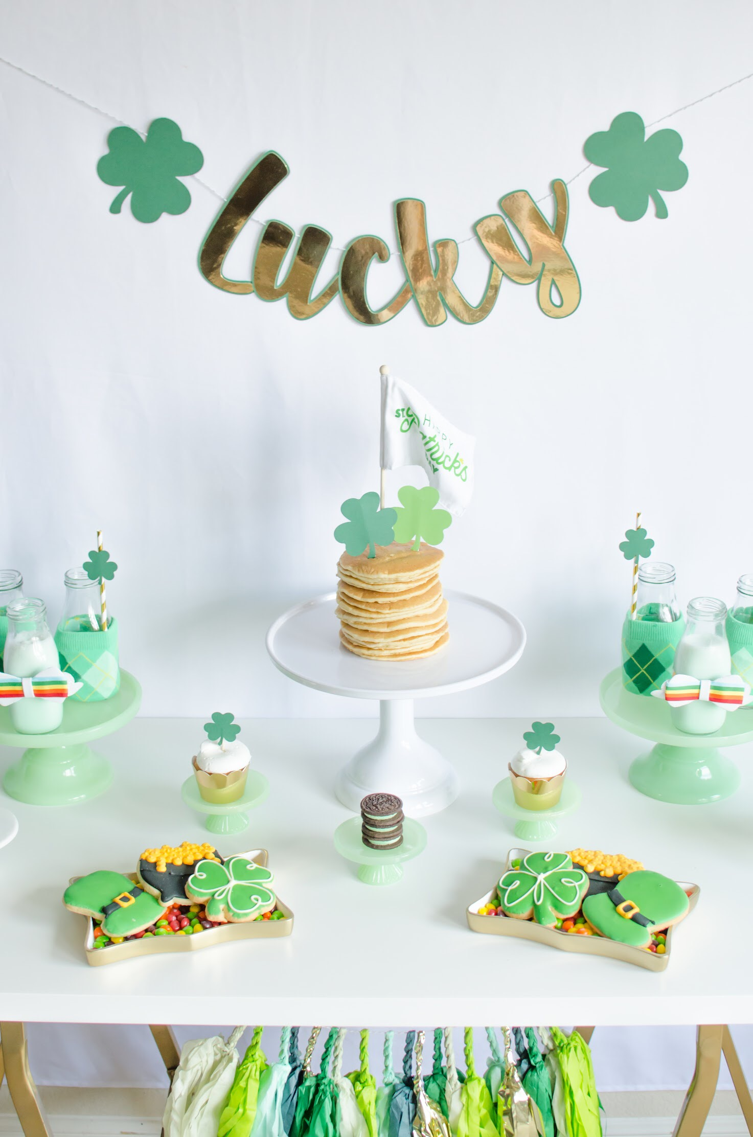 Recreate this Saint Patricks Day tablescape with Mint milkshakes and cute shamrock and horseshoe cupcake toppers. Find all the party details on Mint Event Design www.minteventdesign.com #partyideas #partydecorations #saintpatricksday #stpatricksday #tablescape #desserttable