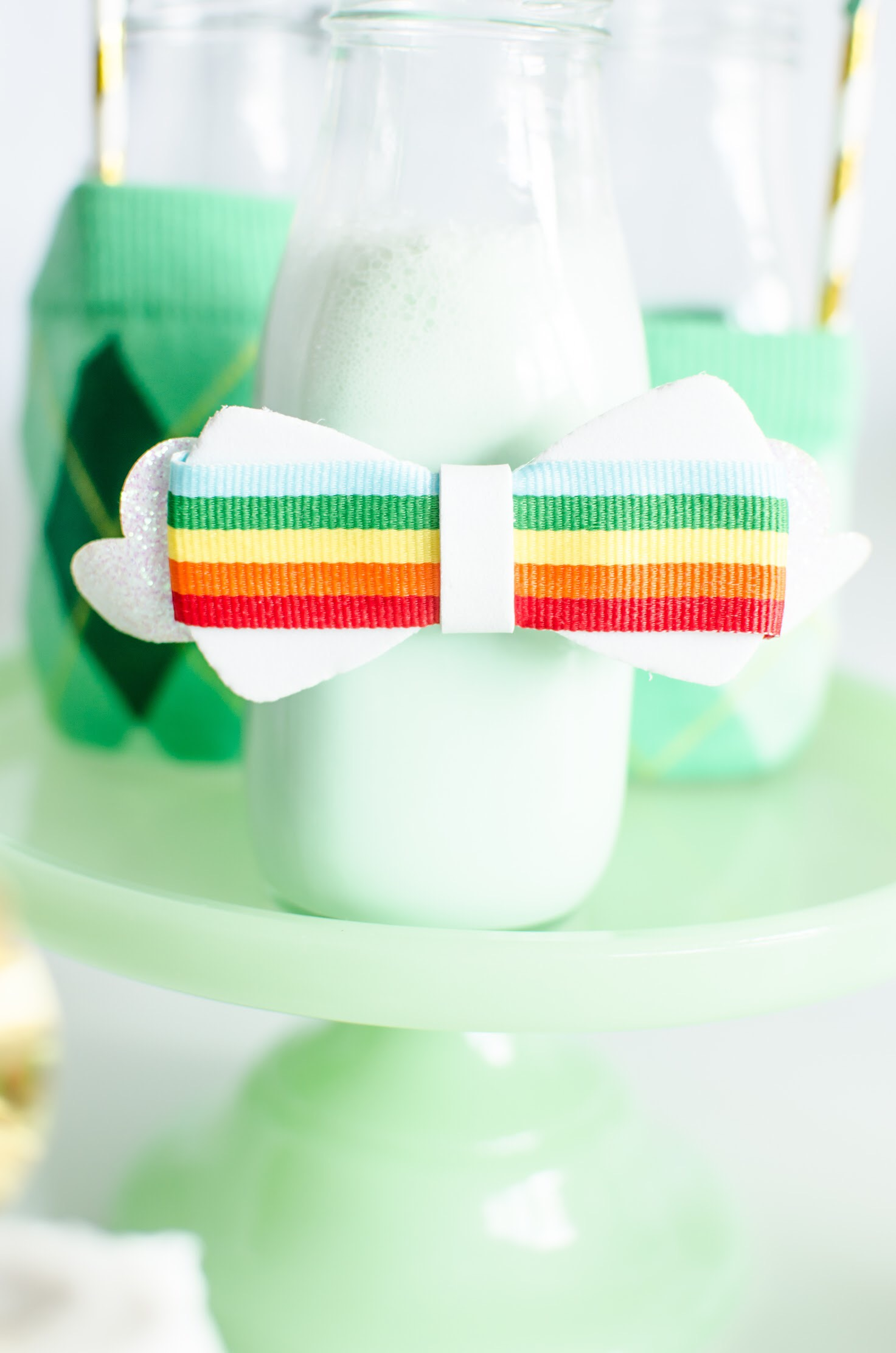 Super cute milk bottle craft for kids - find out how to re-purpose this hair bow for a Saint Patricks Day Party - see the complete diy on Mint Event Design www.minteventdesign.com #partyideas #partydecorations #saintpatricksday #stpatricksday #diycrafts #holidaycrafts #stpatricksdaycraft