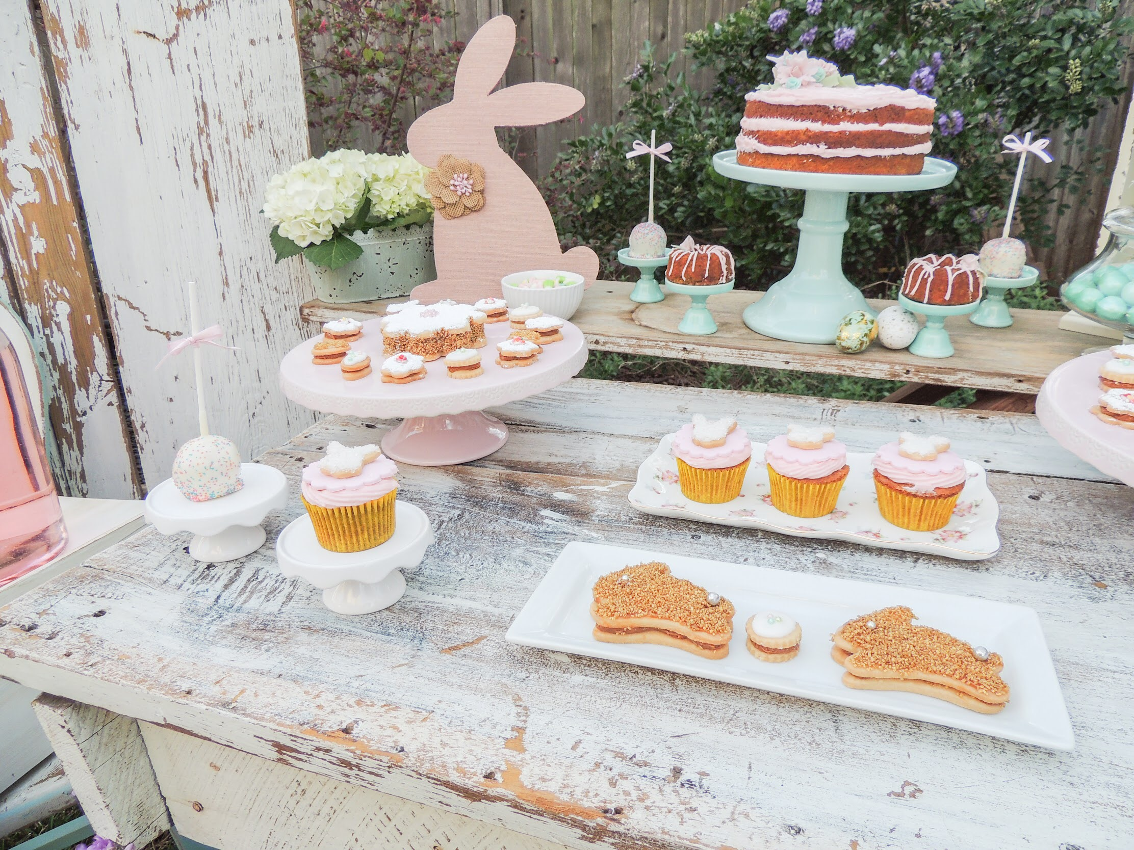 Super cute Easter baking ideas include a tiered carrot cake, mini bundt cakes, cupcakes, petit fours and more.. Styling by Austin Texas Party Planer Mint Event Design www.minteventdesign.com #eastertable #easterdecor #easterparty #partyideas #easterideas #easterdessert