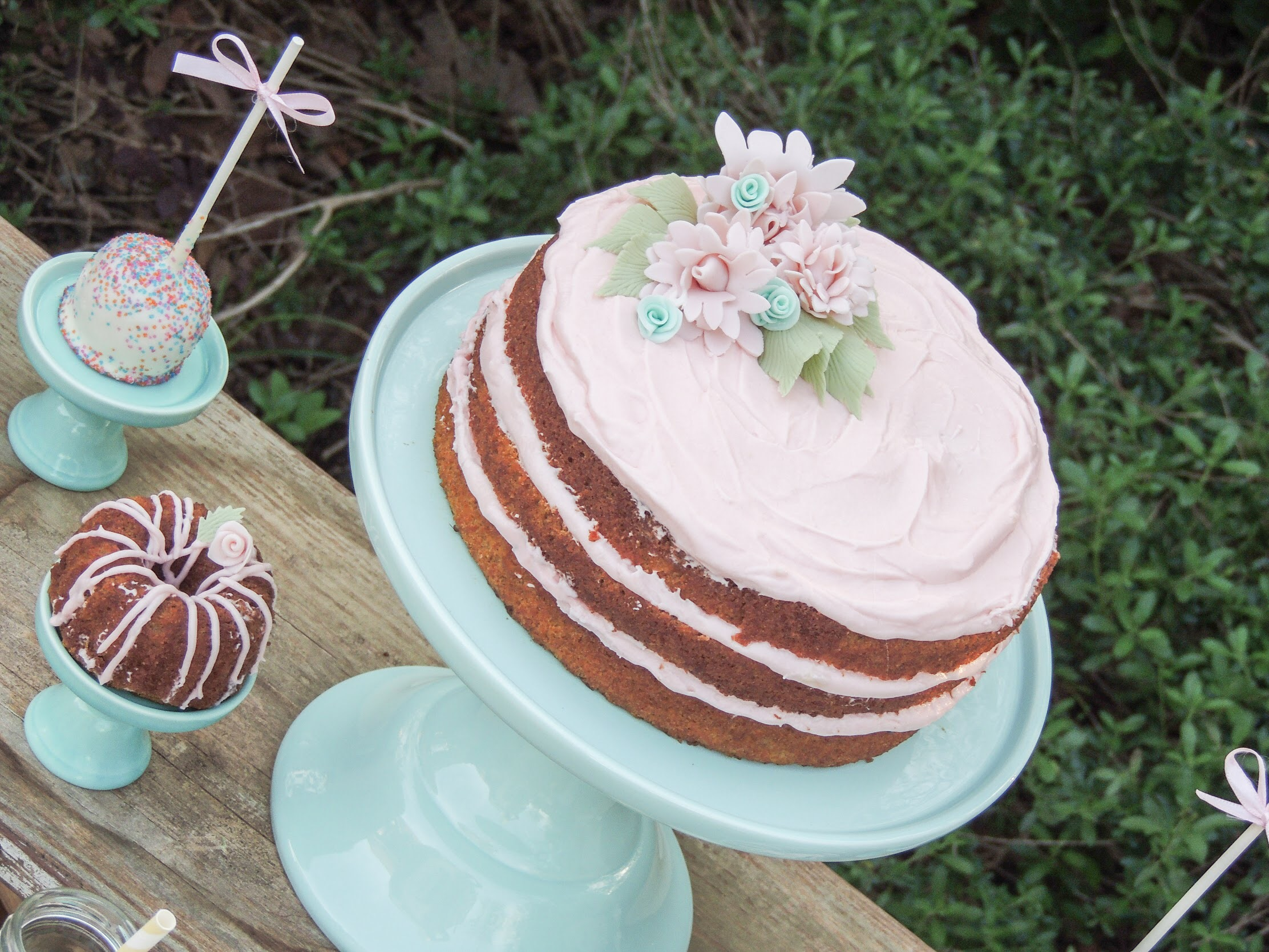 The prettiest of Spring Easter cakes - naked party cake topped with pretty sugar flowers. See more of this Easter Dessert Table on Mint Event Design www.minteventdesign.com #eastertable #easterdecor #easterparty #partyideas #easterideas #partycake