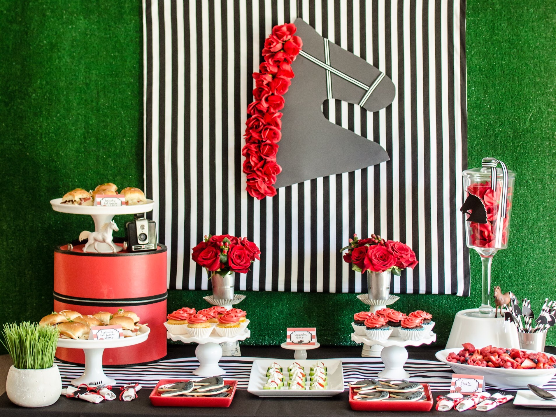 Create the perfect party table backdrop for your Kentucky Derby Party with this striped background and faux grass with a horse silhouette wearing red roses on its mane. Styling by party planner Mint Event Design in Austin Texas www.minteventdesign.com #kentuckyderbyparty #kentuckyderby #partyideas #derbyday #runfortheroses #partytable #partybackdrop