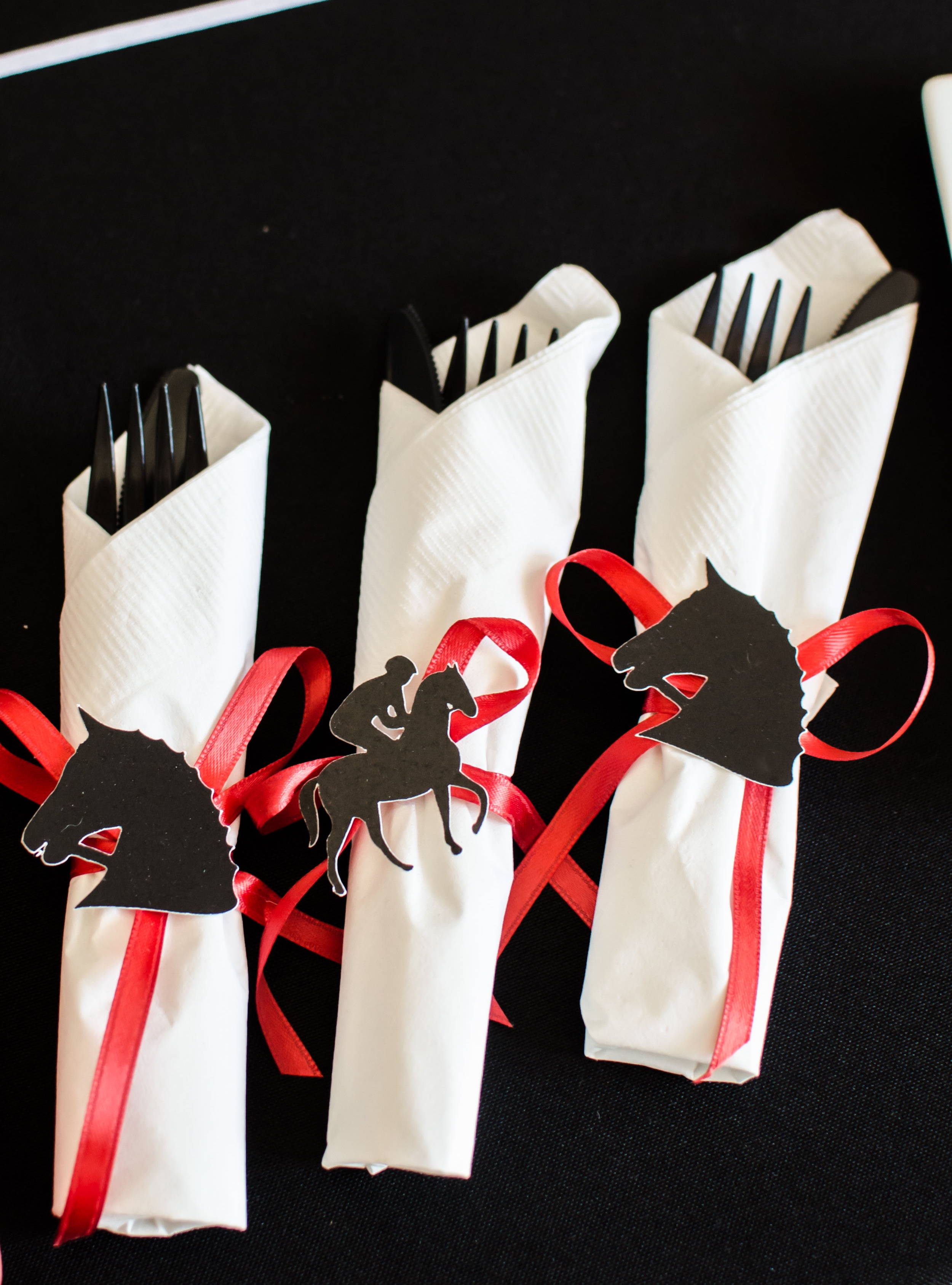 Cute Kentucky Derby themed party cut outs are perfect added to napkins that are tied together with red ribbon. Styling by Mint Event Design www.minteventdesign.com