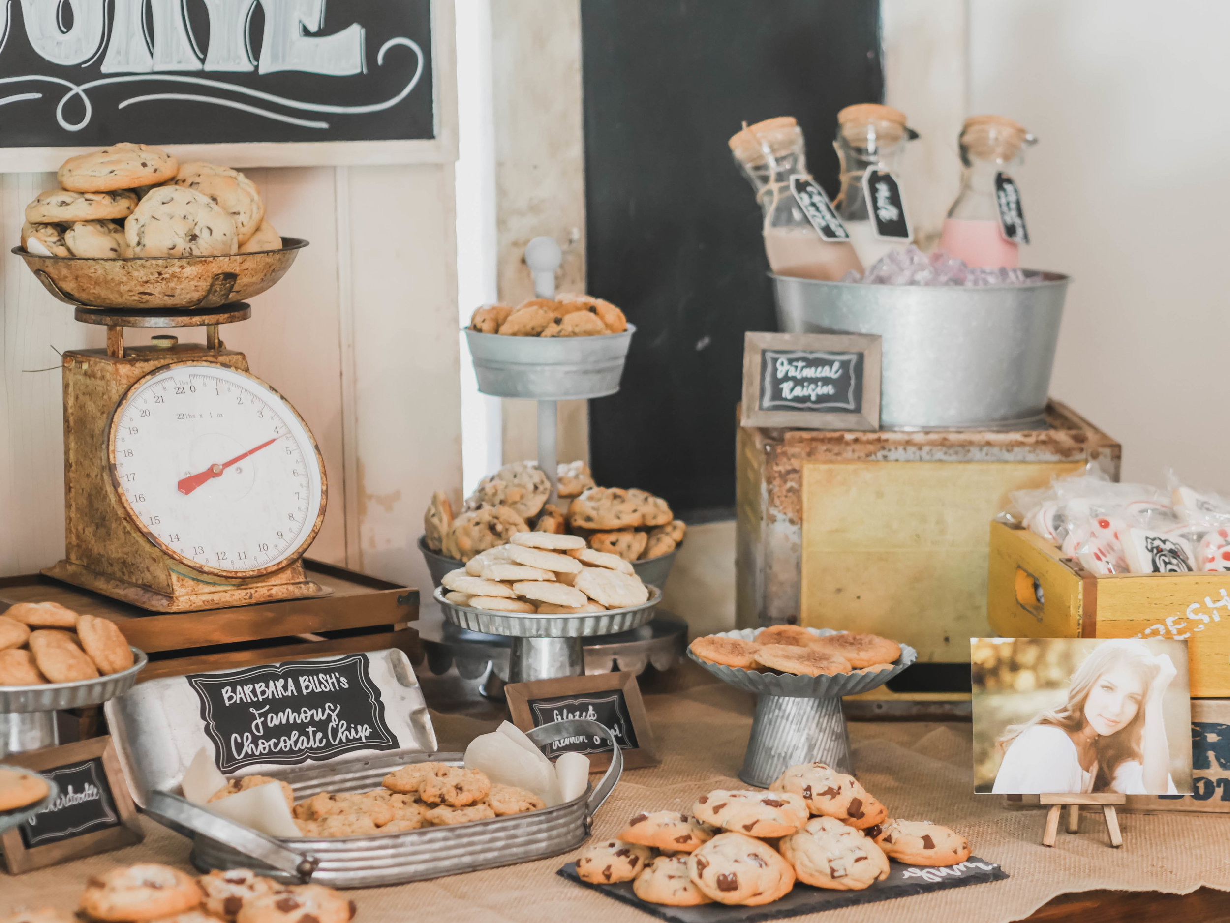 Rustic serving platters and galvanized metal create the perfect farmhouse feel at this One Smart Cookie Graduation party by Mint Event Design - party planner in Austin Texas www.minteventdesign.com #graduationparty #graduationpartyideas #partyideas #rusticpartyideas #partyinspiration #chalkboardsigns #desserttable