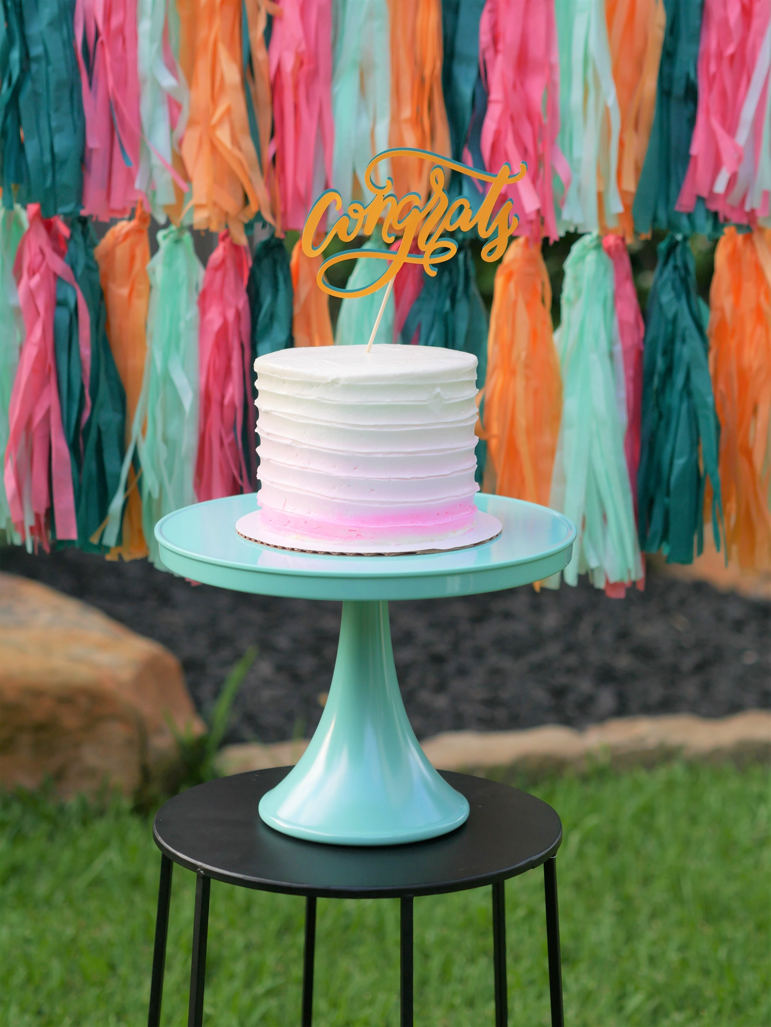 Tres leches cake and banner backdrop with tissue tassel garlands to match the party colors. See more from this Grad Party on Mint Event Design www.minteventdesign.com #graduationparty #graduationpartyideas #graduation #gradparty #gradpartyideas #partydecor #graduationcake