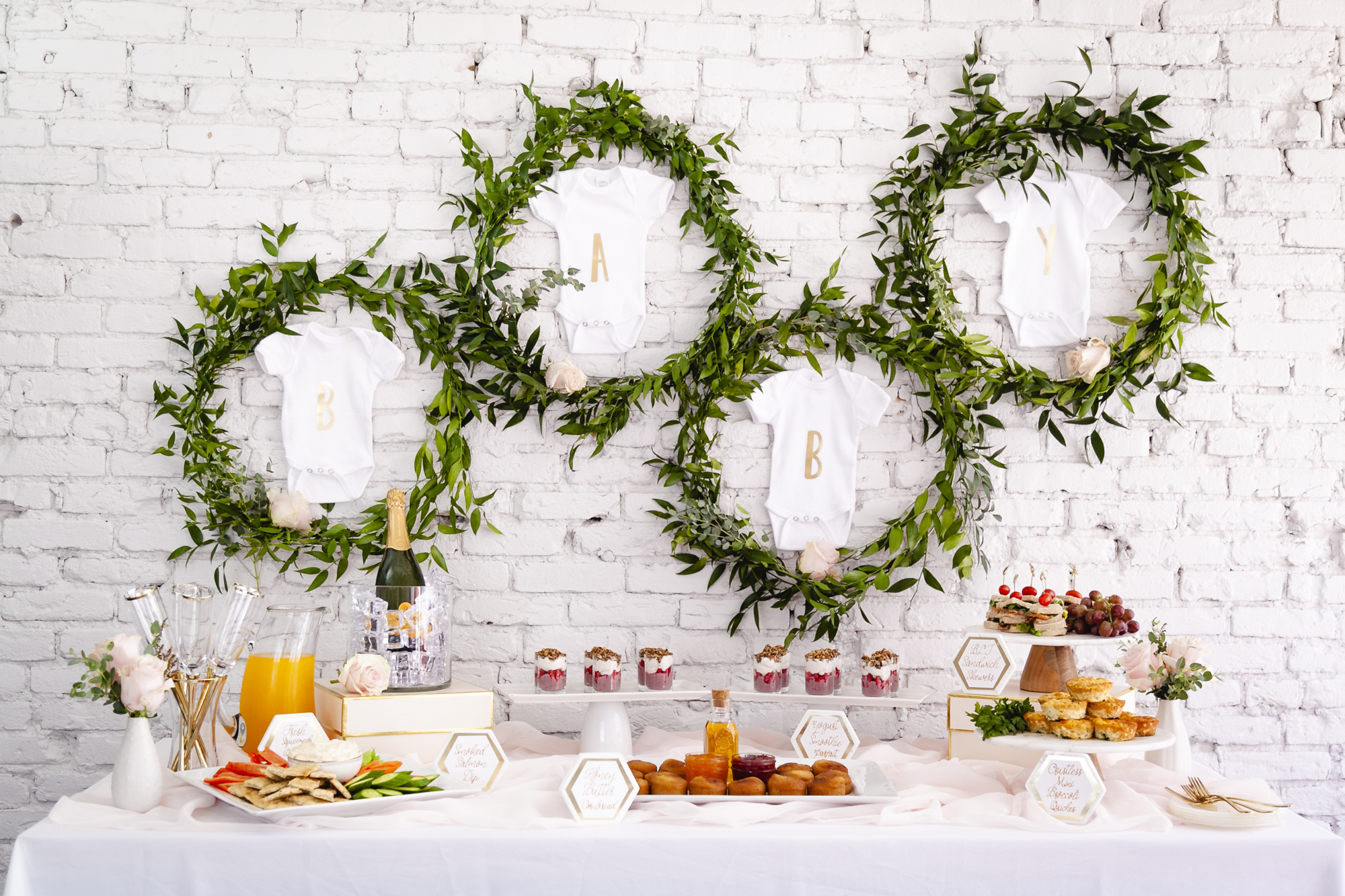 "Elegant Baby Shower Sip and See ideas. The food table backdrop was created with greenery wreaths and baby onesies hanging inside with the letters for ""BABY"" on them in gold. Styling by Mint Event Design in Austin Texas for Bento Picnic www.minteventdesign.com"