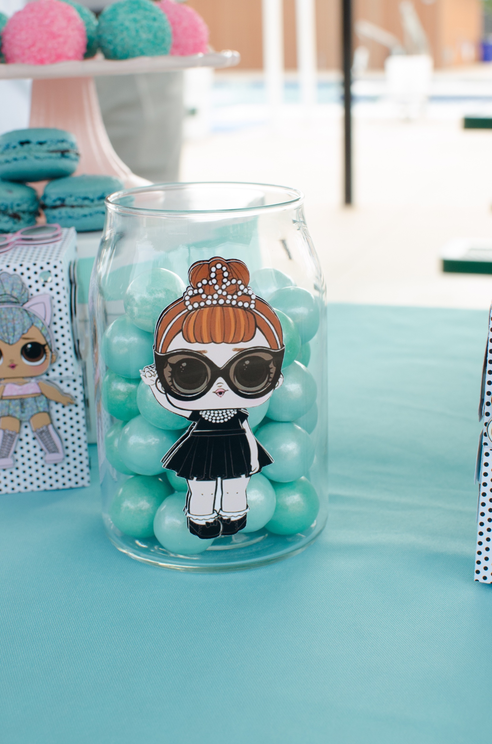 Fun candy jar for a LOL Doll Inspired Birthday Party with doll character cut outs. Party styling by Mint Event Design www.minteventdesign.com